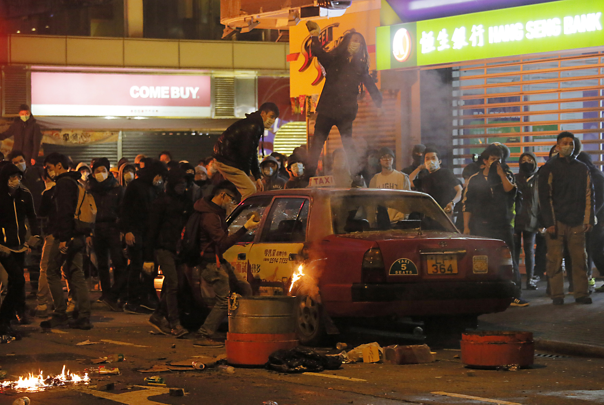 Rioters throw bricks at police in Mong Kok district of Hong Kong, Tuesday, Feb. 9, 2016. Hong Kong's Lunar New Year celebration descended into chaotic scenes as protesters and police clashed over a street market selling fish balls and other local holiday delicacies. (AP Photo/Vincent Yu)