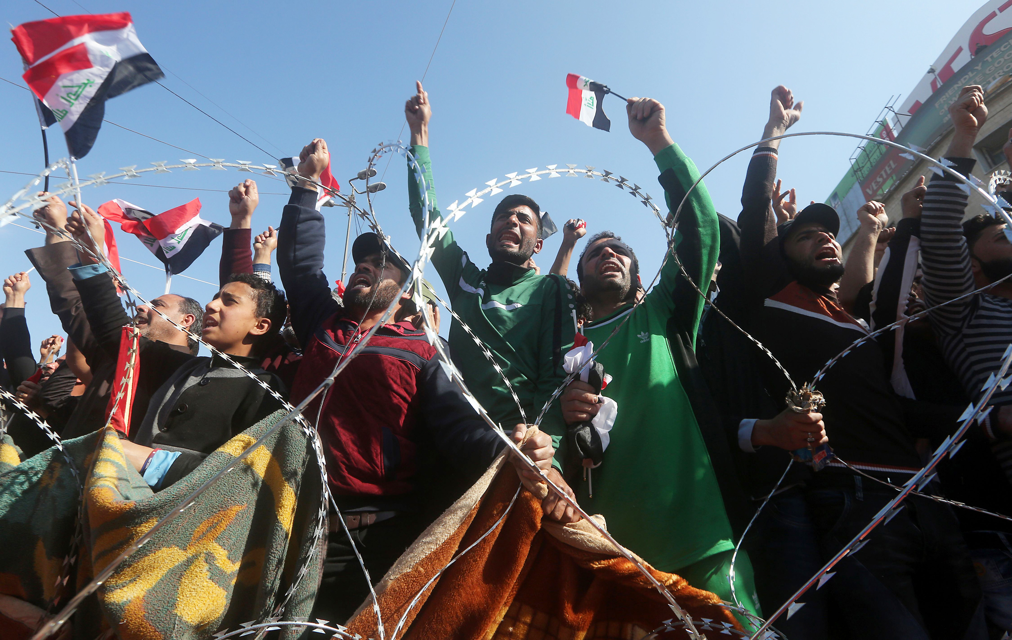 Iraqi supporters of Shiite cleric Moqtad...Iraqi supporters of Shiite cleric Moqtada al-Sadr wave the national flag as they listen to his speech during a demonstration in Baghdad's Tahrir Square on February 26, 2016, calling for governmental reform and elimination of corruption. / AFP / AHMAD AL-RUBAYEAHMAD AL-RUBAYE/AFP/Getty Images