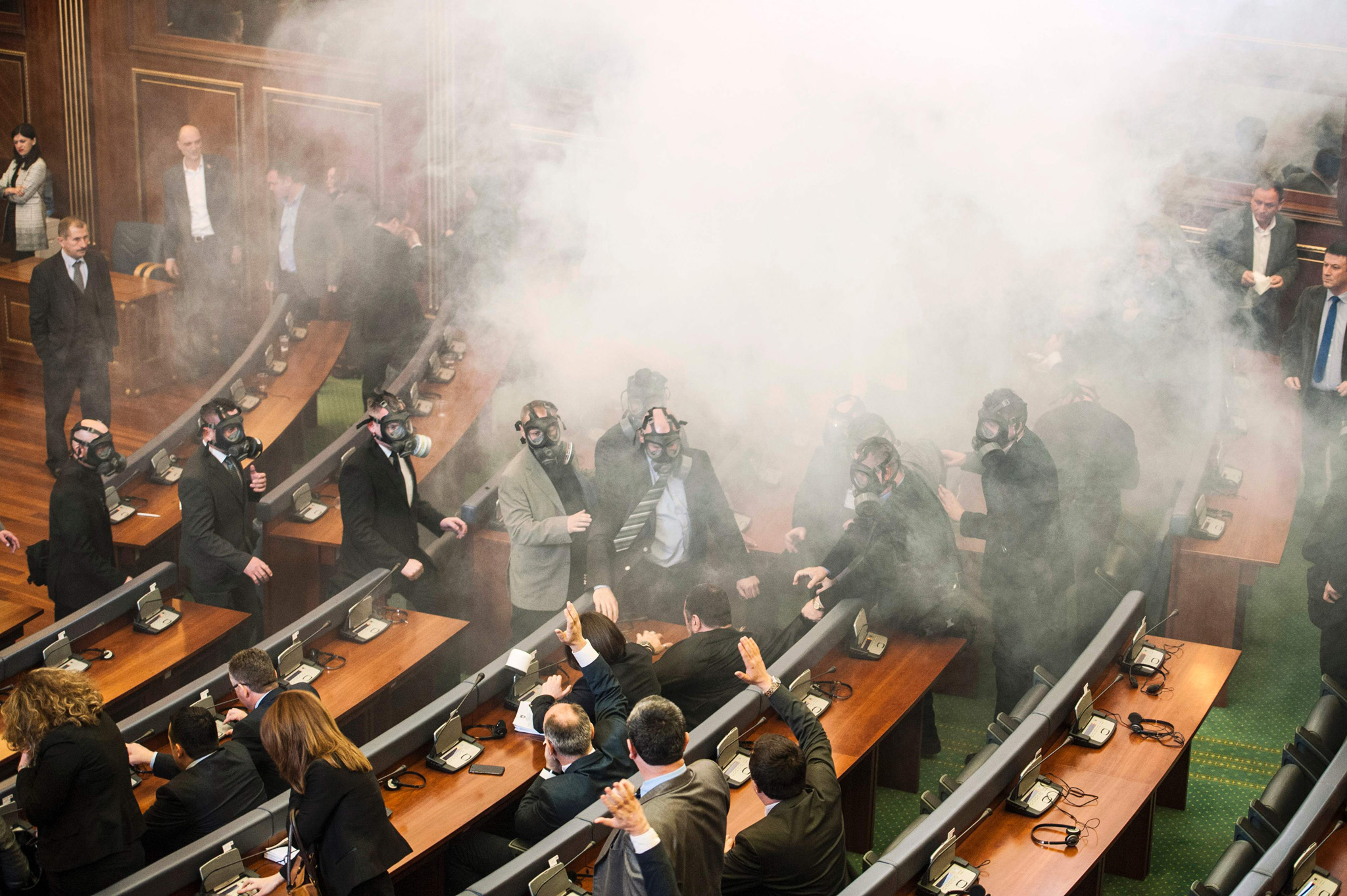 Kosovo police officers weeraing  gas masks inspect the parliament, after tear gas was launched by opposition lawmakers, disrupting the first parliamentary session of the year