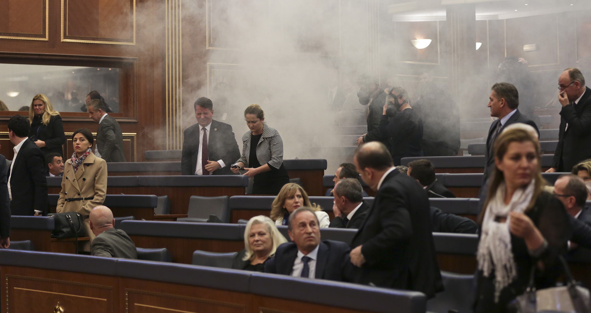 Smoke fills the auditorium of the Kosovo assembly after opposition lawmakers released tear gas canisters disrupting a parliamentary session in Kosovo capital Pristina on Friday Feb. 26, 2016. Kosovo opposition members have released tear gas inside Parliament as the lawmakers were readying to vote on wether to elect Hashim Thaci , foreign minister and former guerrilla leader, as the next president. (AP Photo/Visar Kryeziu).