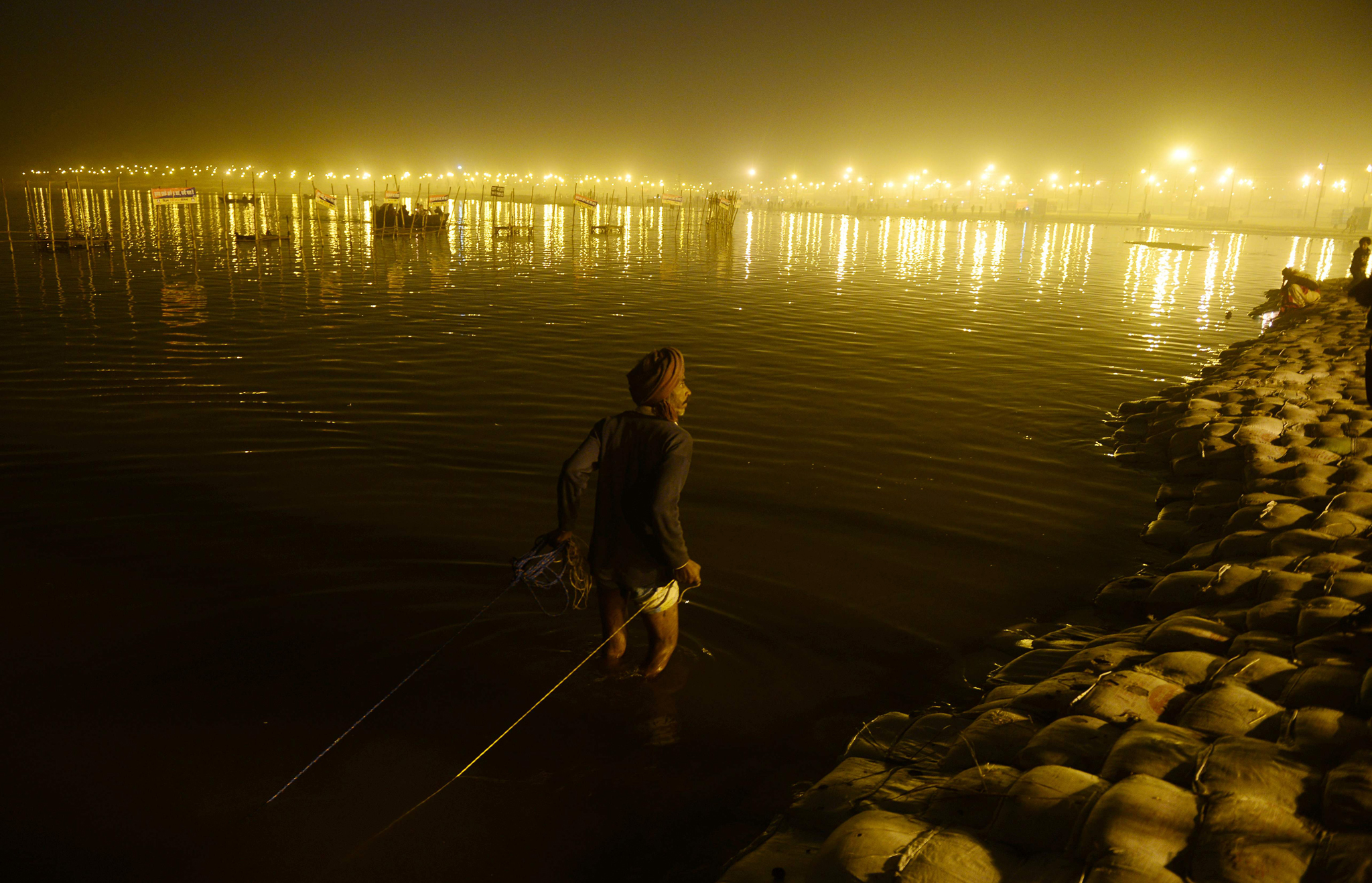 TOPSHOT - An Indian scavenger searches f...TOPSHOT - An Indian scavenger searches for coins offered by Hindu devotees at Sangam during the annual Magh Mela festival in Allahabad on February 5, 2016