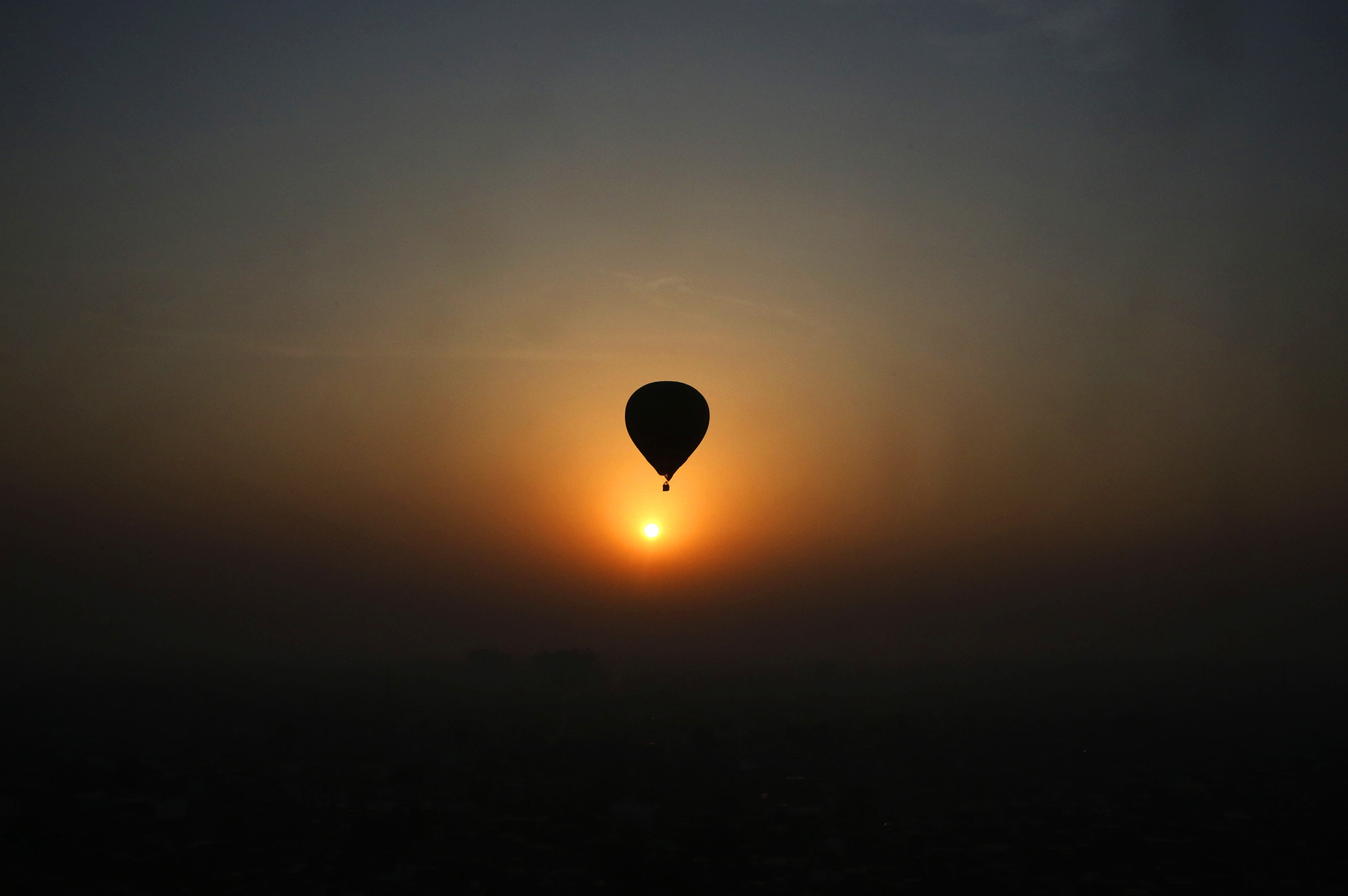 A hot air balloon flies against the sun rise during Lucknow balloon festival in Lucknow, India