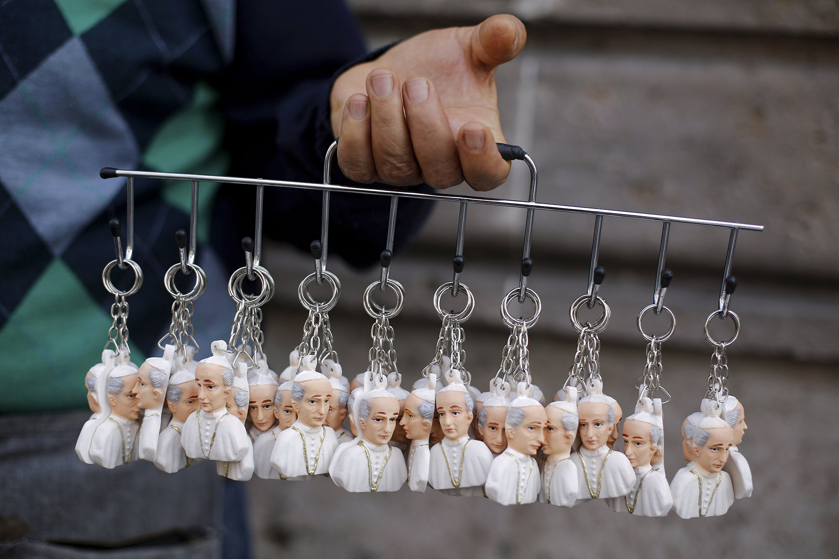 A man sells key-chains in the shape of Pope Francis in downtown Morelia