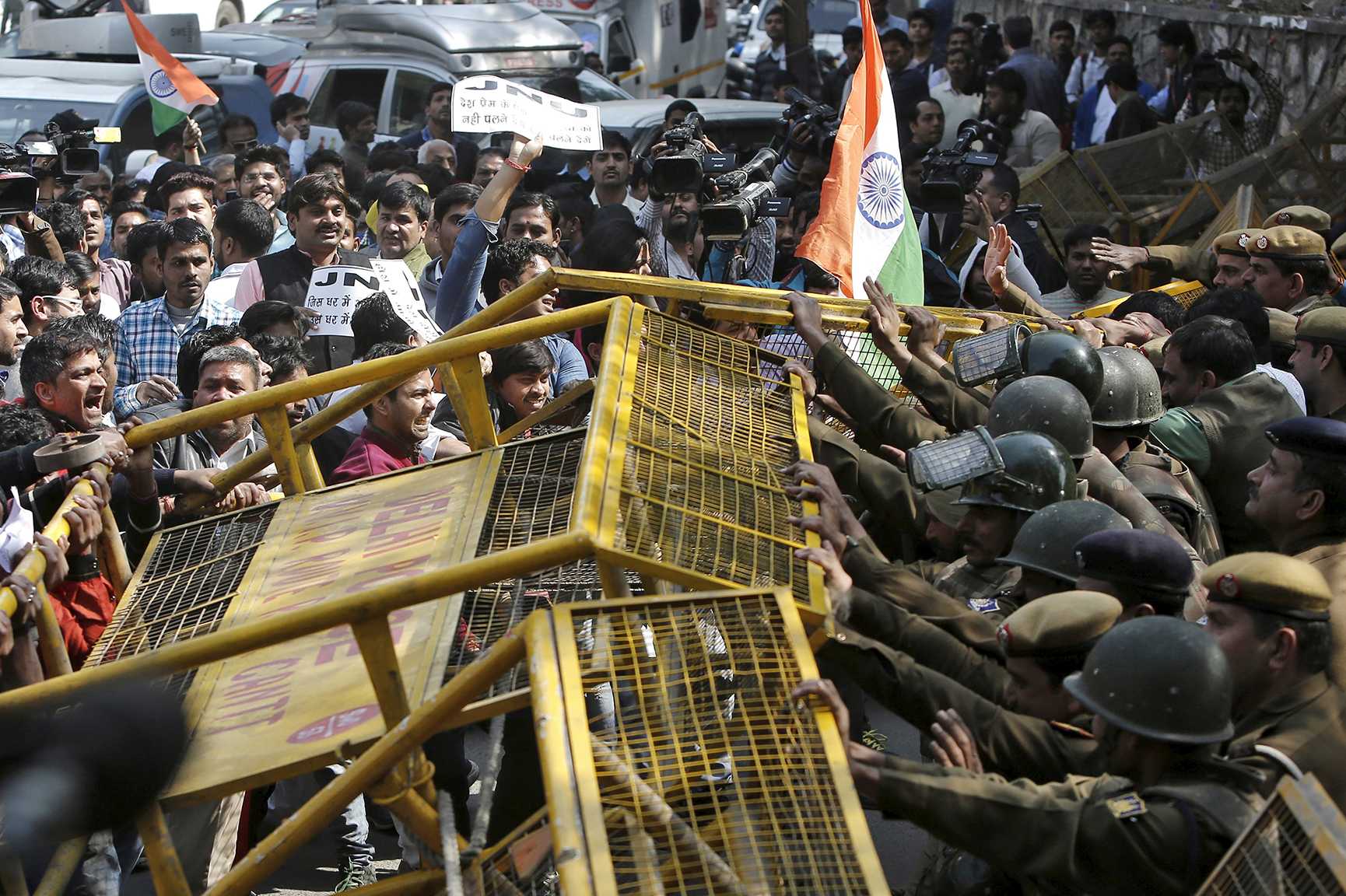 Police stop activists from various Hindu right-wing groups as they try to cross a barricade during a protest against the students of JNU outside the university campus in New Delhi