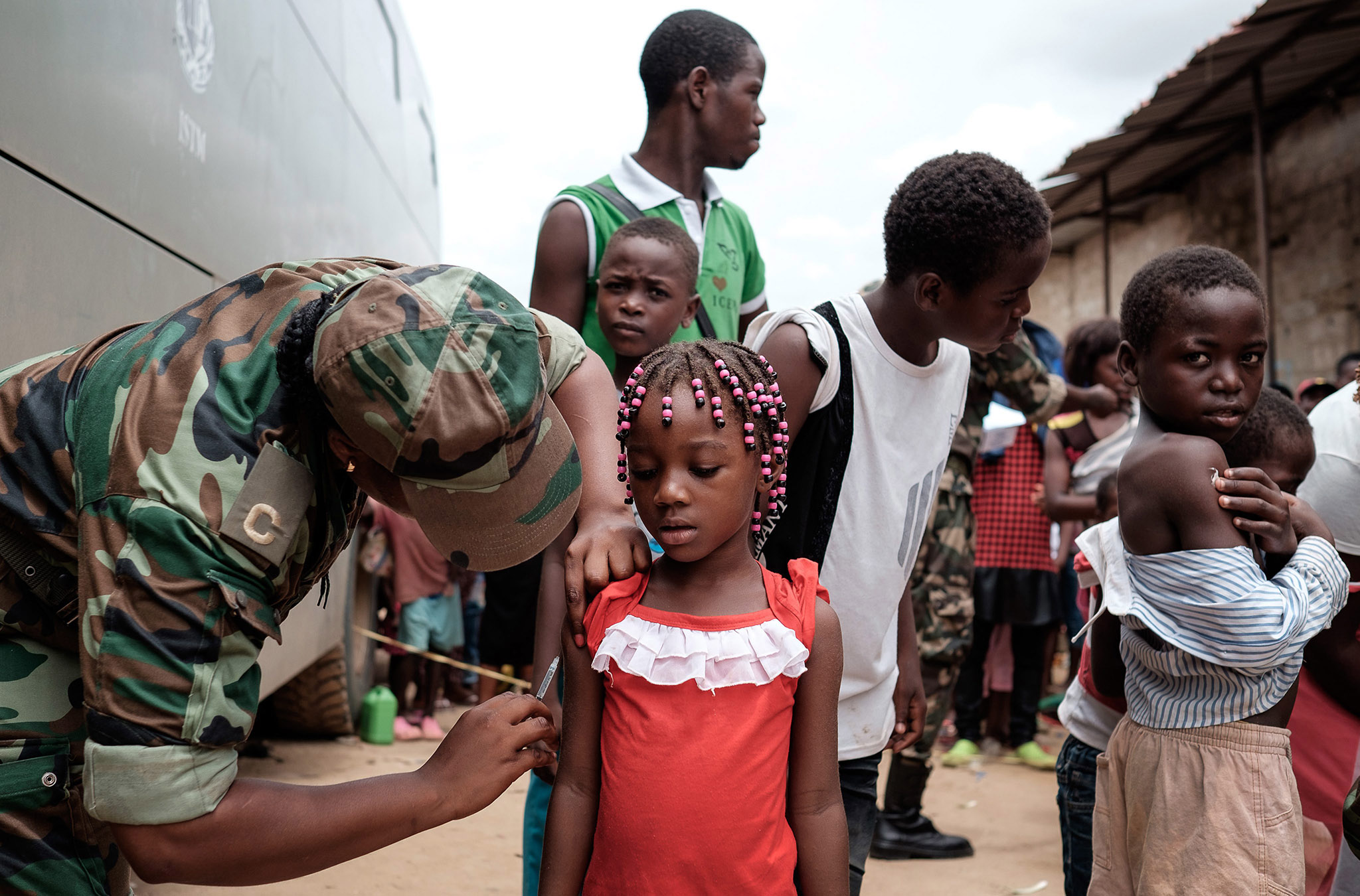 A Angolan military administers a yellow fever vaccine to a child at 'Quilometro 30' market, Luanda, Angola