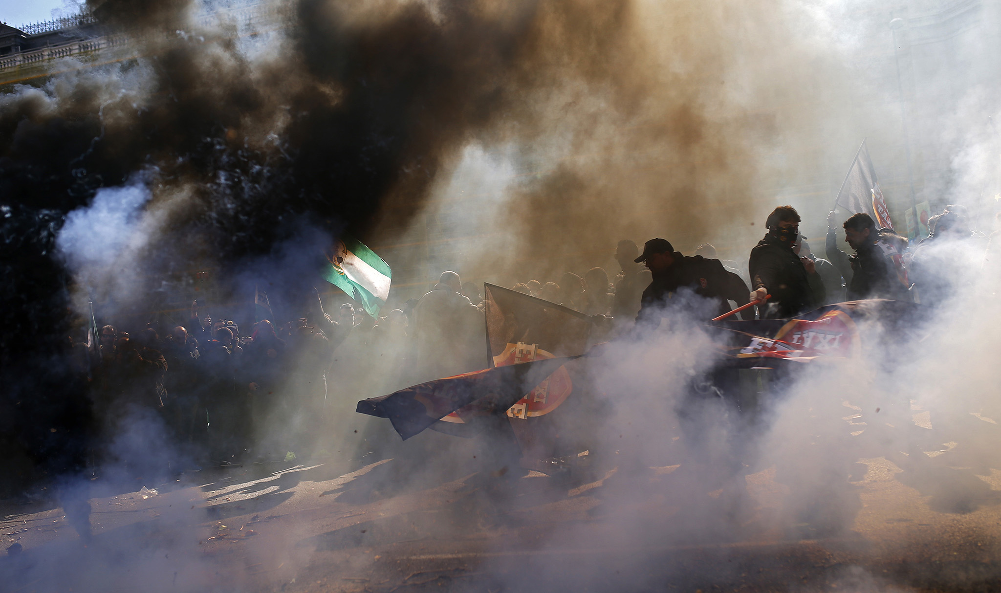 People surrounded by smoke wave flags and shout slogans during a protest by a Spanish taxi drivers' union in Madrid