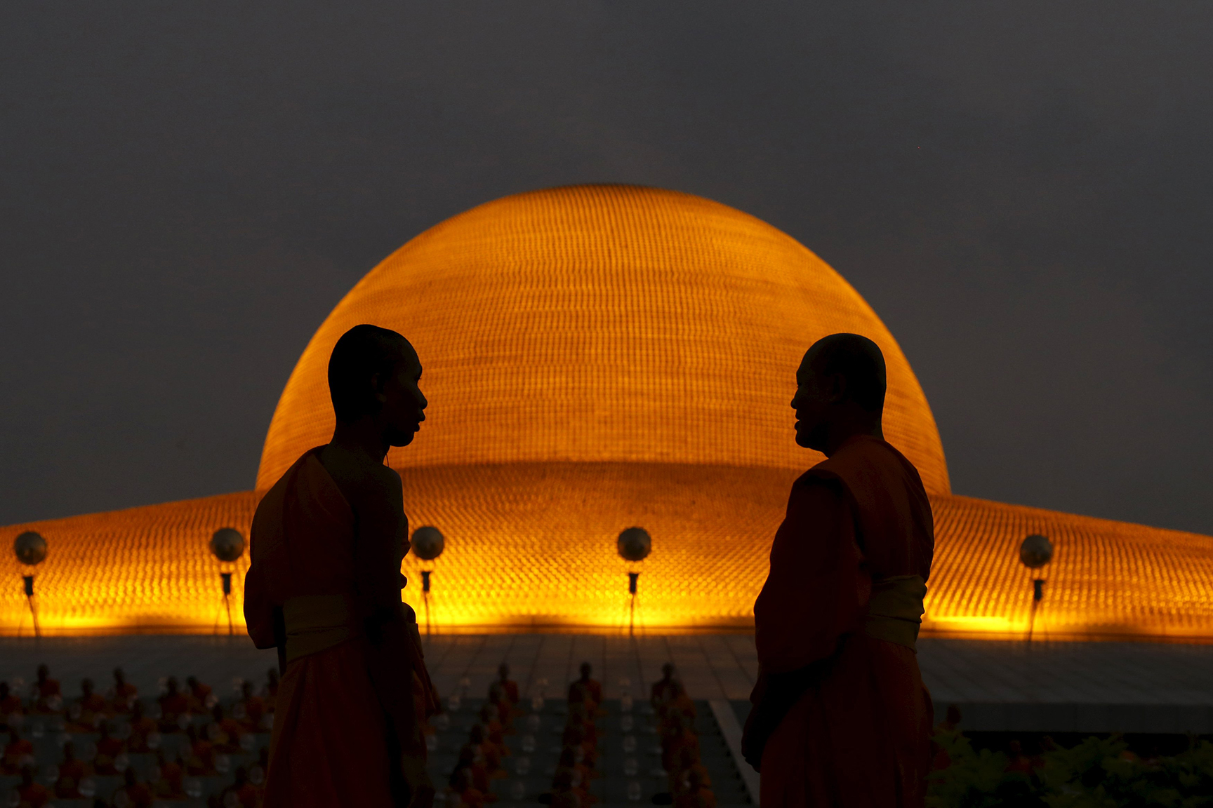 A Buddhist monk stands in front of the Wat Phra Dhammakaya temple in Pathum Thani province, north of Bangkok before a ceremony on Makha Bucha Day