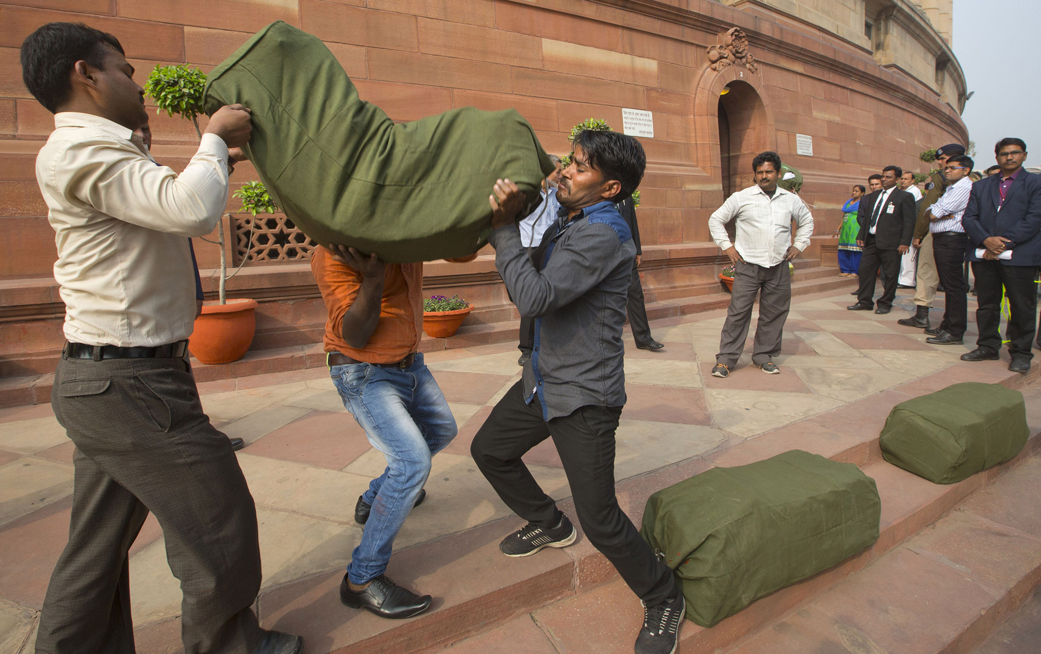 Indian workers carry a bag containing copies of the federal budget for the year 2016-17, that will be distributed to lawmakers at the parliament house in New Delhi, India.