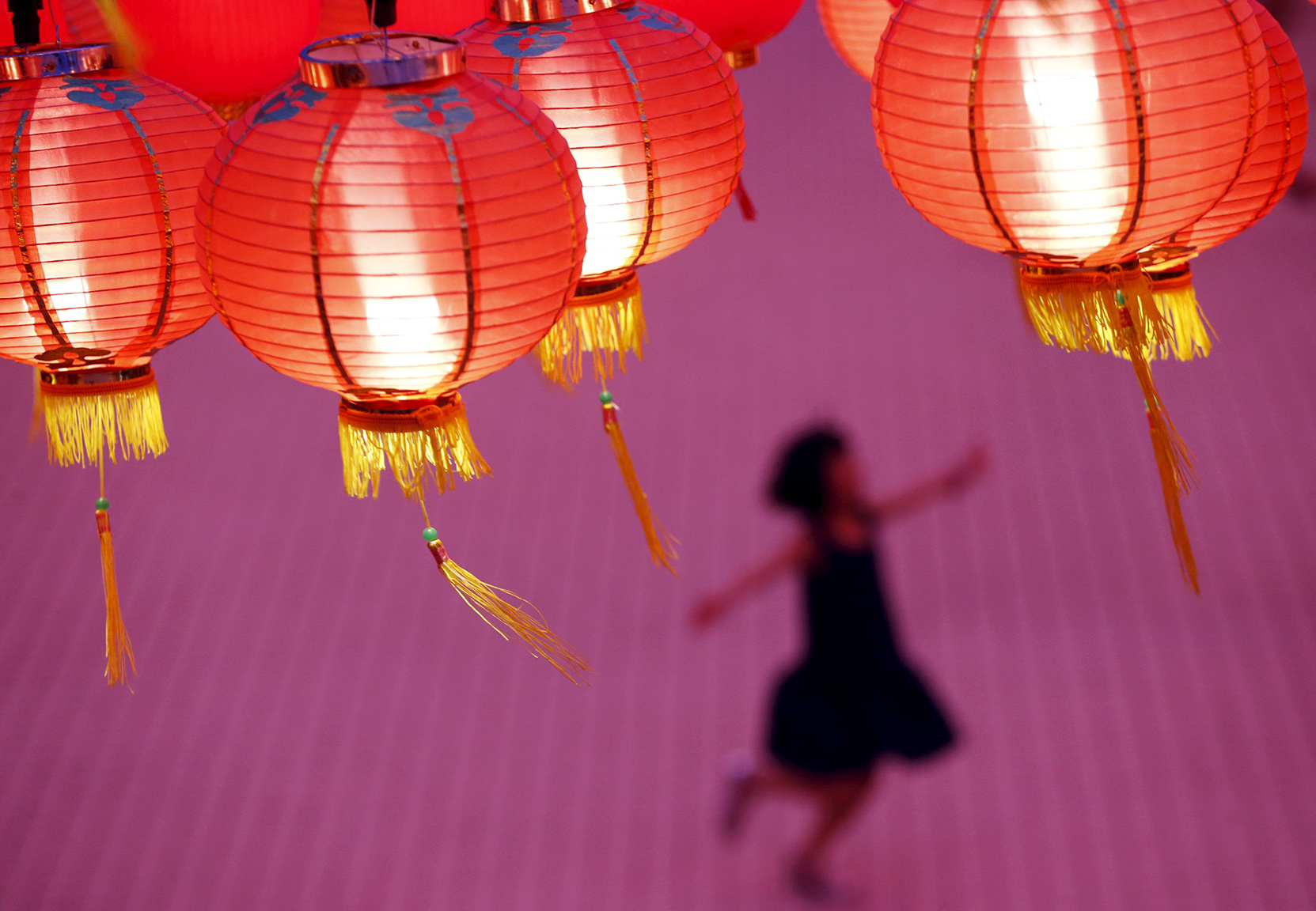 A child plays beneath lanterns at a temple decorated to celebrate the Chinese New Year in Kuala Lumpur, Malaysia