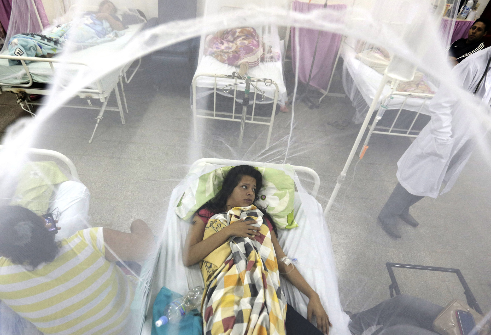 Protected by a mosquito net, Nadia Gonzalez recovers from a bout of dengue fever at a hospital in Luque, Paraguay Friday, Feb. 5, 2016. Dengue, like the Zika virus, is transmitted by the same vector, the Aedes aegypti mosquito. Zika was discovered in a Ugandan forest in 1947 and until last year, the virus had never caused serious disease. It has now spread to more than 20 countries. (AP Photo/Jorge Saenz)