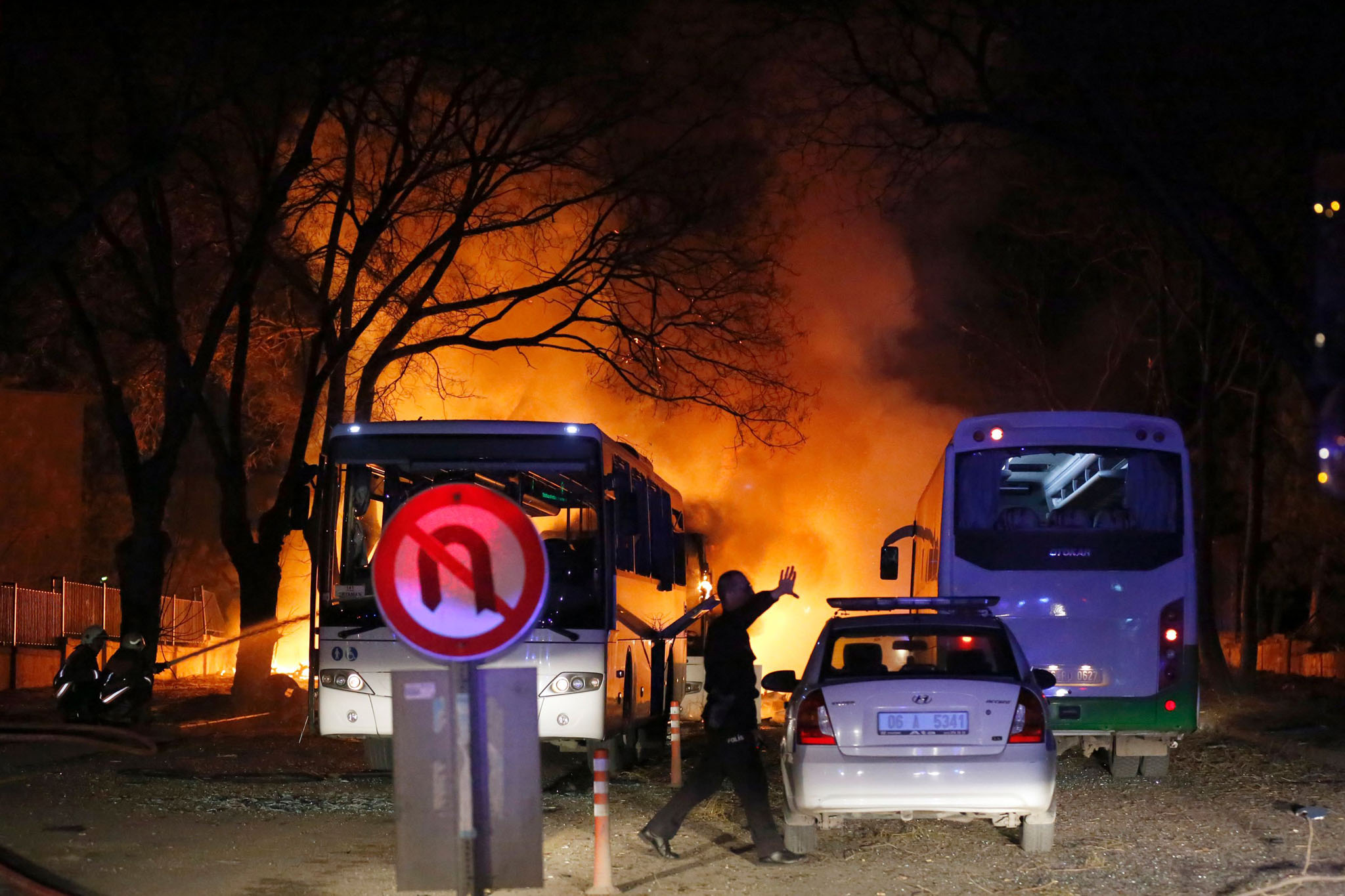 A police officer gestures as he walks at the site of an explosion while firefighters try to extinguish flames after an attack targeted a convoy of military service vehicles in Ankara