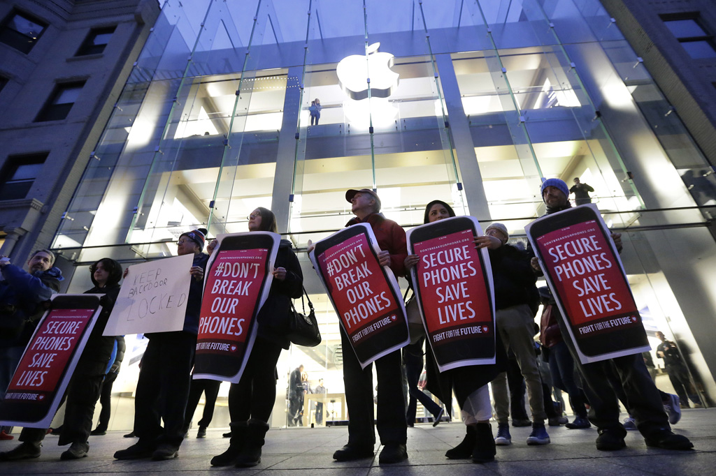 Protesters carry placards outside an Apple store