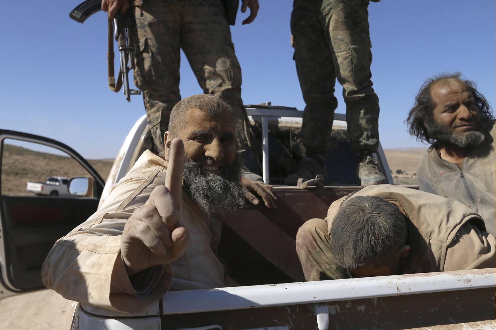 An Islamic State fighter gestures while being held as prisoner with fellow fighters under Democratic Forces of Syria fighters as they ride a pick-up truck near al-Shadadi town, Hasaka countryside
