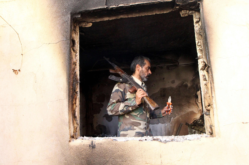 A fighter loyal to Libya's internationally recognised government checks a damaged house in Benghazi