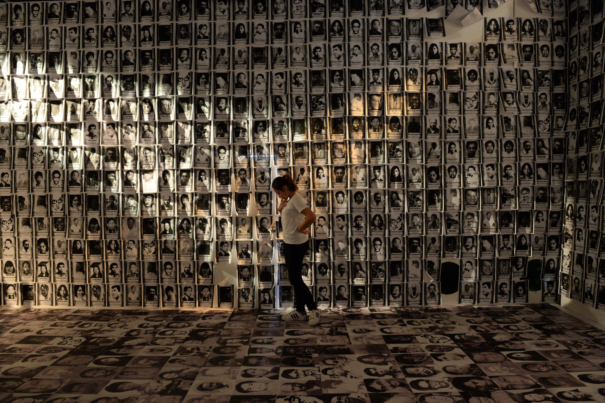 A woman stands among photos taken of human rights victims during martial law, displayed at an experiential museum inside a military camp in Manila