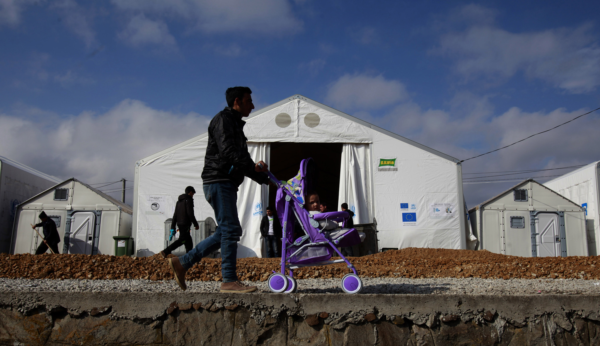A man pushes a baby in a stroller in front of tents at the transit center for refugees near northern Macedonian village of Tabanovce