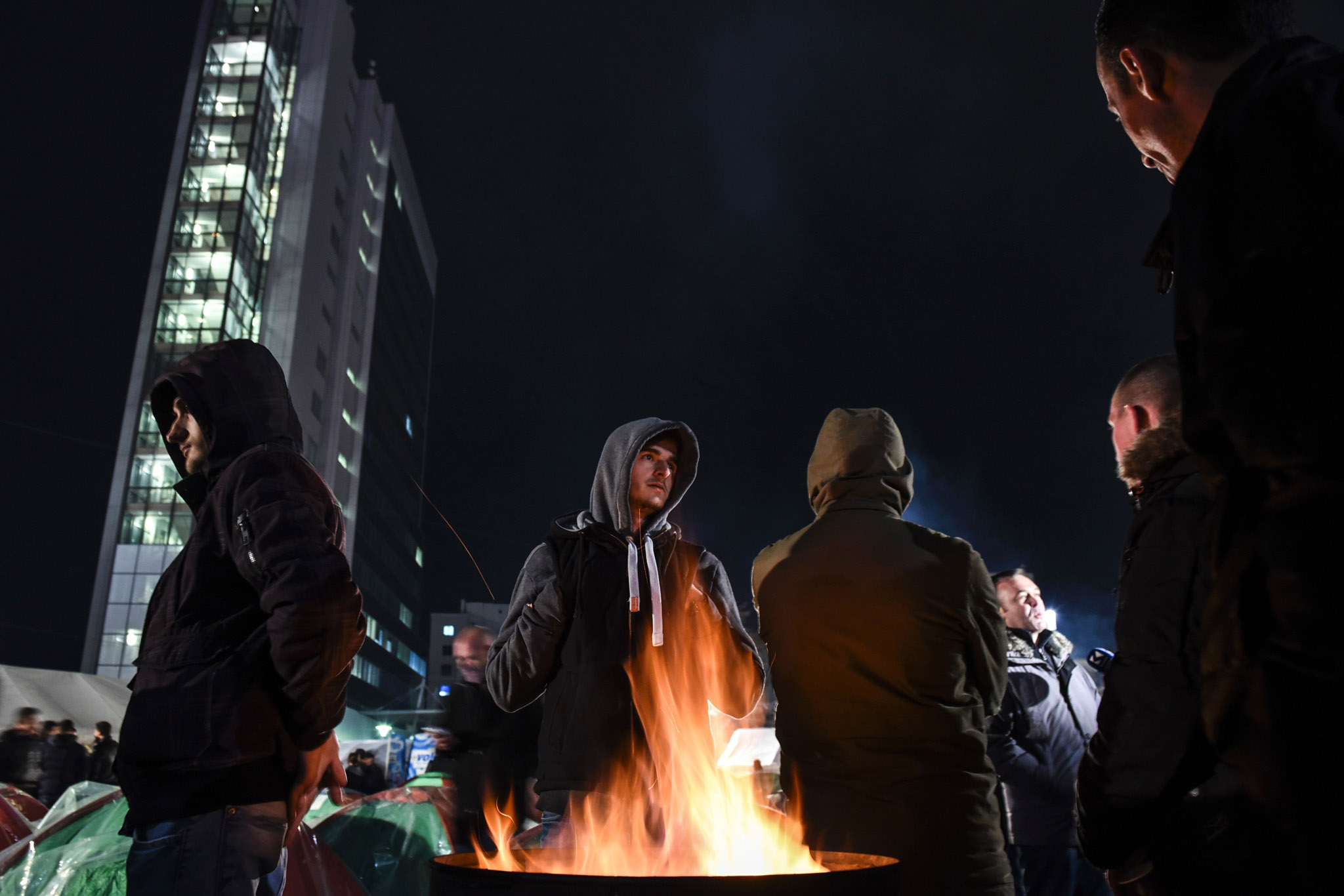 Opposition party supporters keep warm by a fire as they gather in front of Kosovo's government building in Pristina