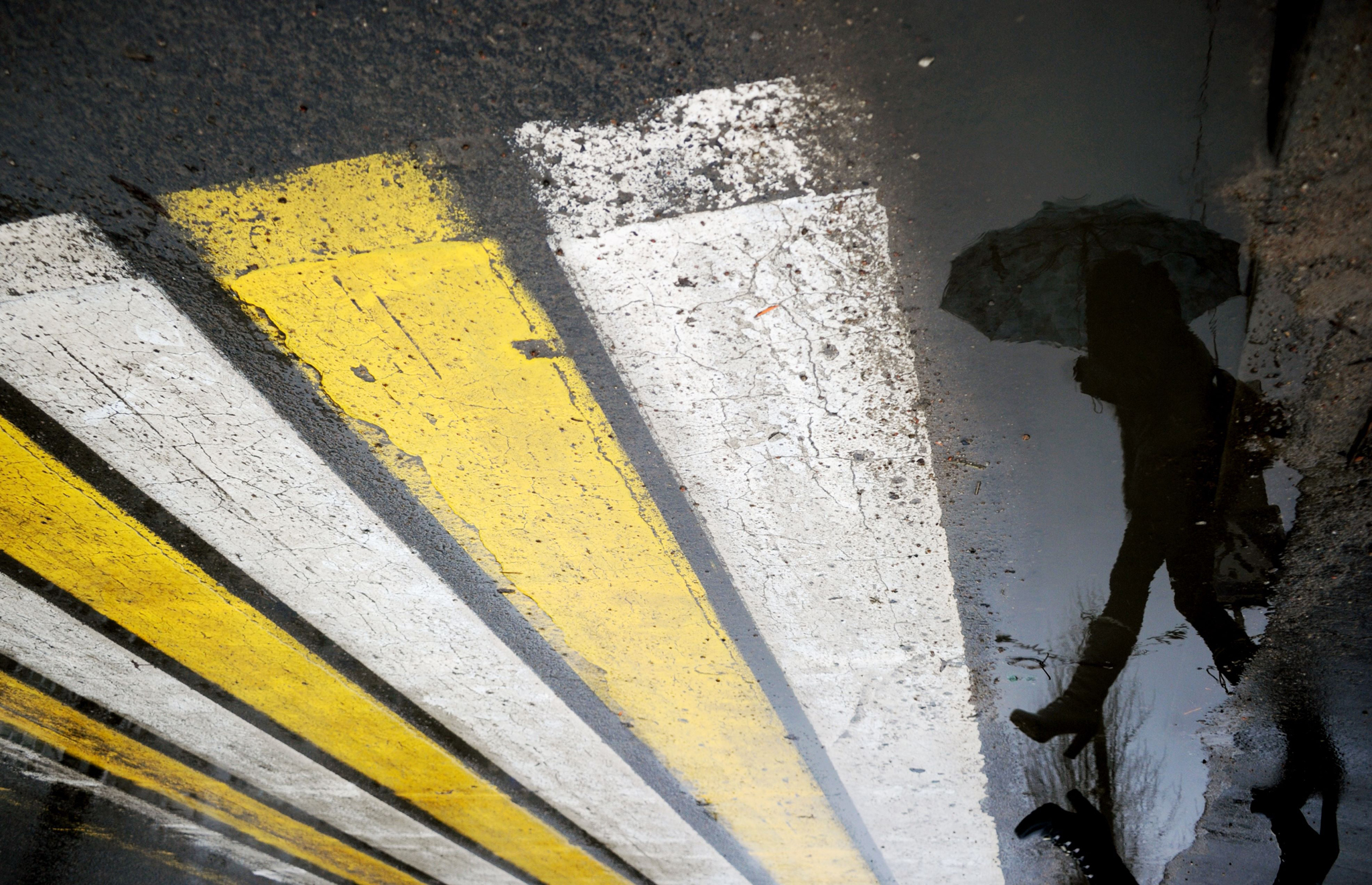 A woman is reflected in a puddle as she crosses a road in Minsk, during warm winter weather