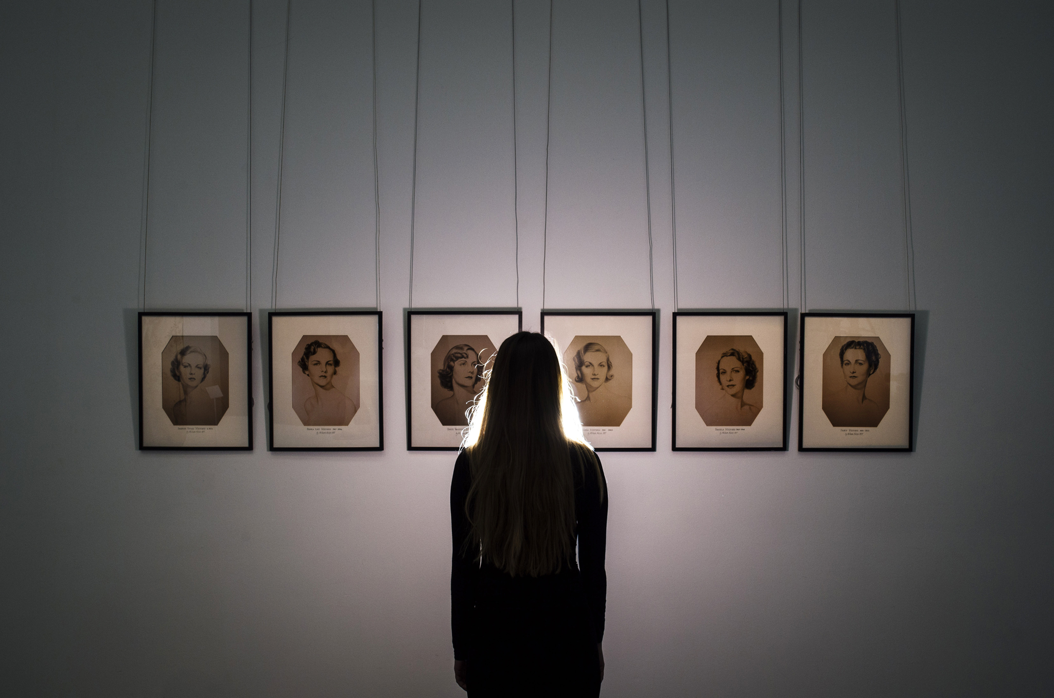 A Sotheby's employee stands infront of a series of portraits of the Mitford Sisters during the pre-auction preview of the personal collection of Deborah Cavendish, Duchess of Devonshire at Sotheby's