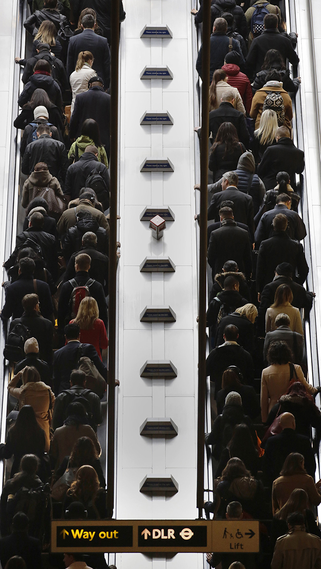 Passengers ride an escalator at Canary Wharf tube station in London