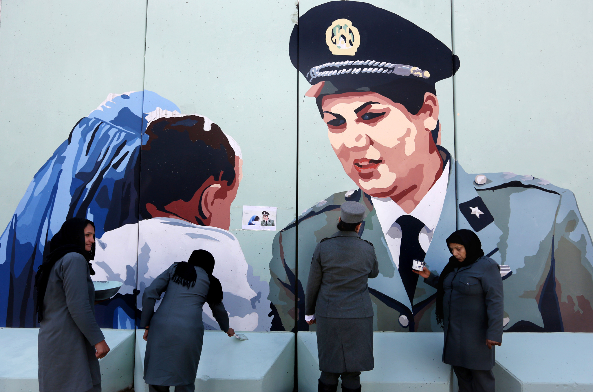 Friba Hameed, 30, an Afghan police officer, second right, helps paint part of a mural of herself on a wall outside the main gate of a police precinct to mark International Women's Day in Kabul, Afghanistan, Tuesday, March 8, 2016. (AP Photo/Rahmat Gul)