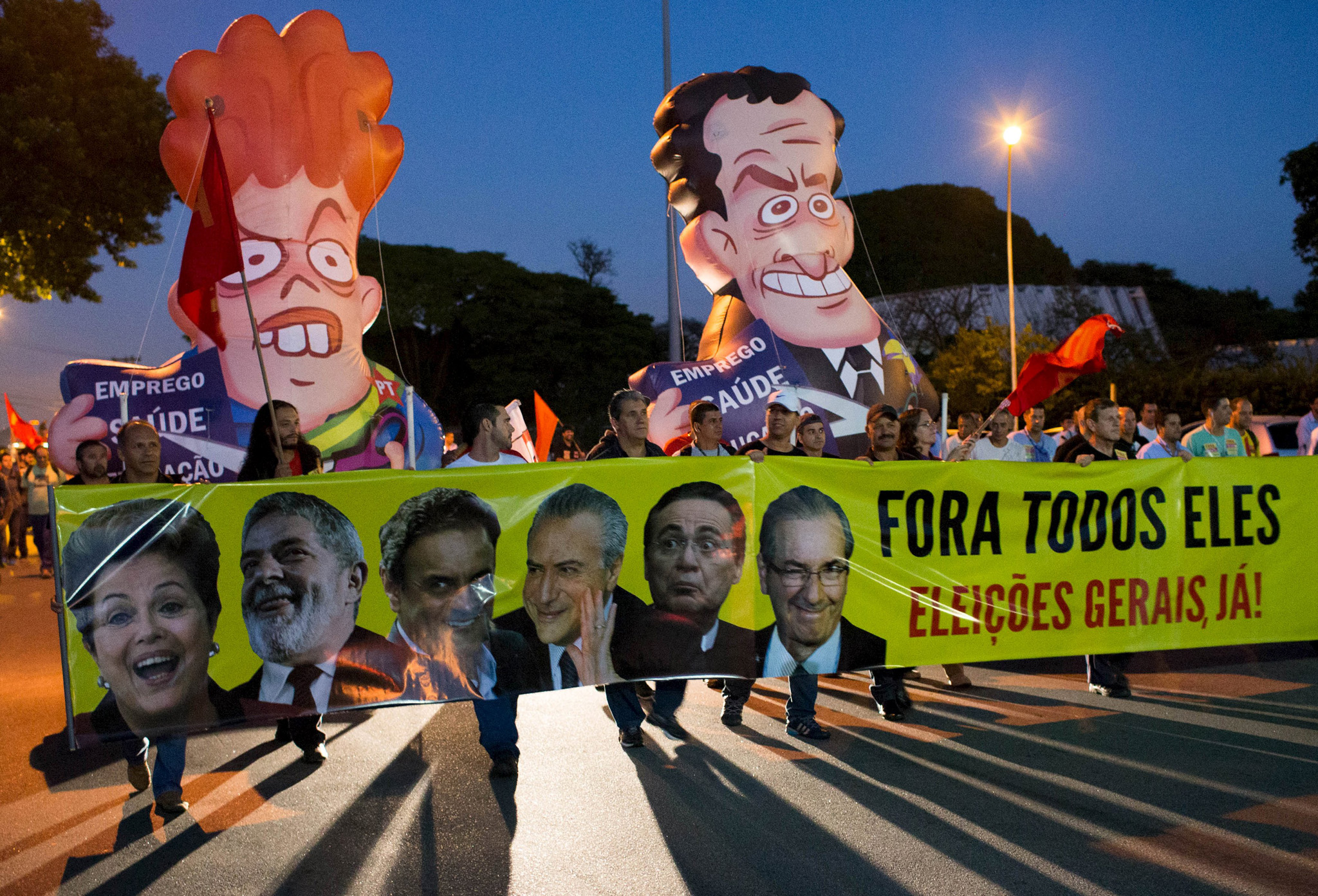 "Workers of General Motors march against Brazil's President Dilma Rousseff,  former president Luiz Inacio Lula da Silva and oppositions as they carry inflatable dolls depicting Rousseff (L) and opposition senator Aecio Neves, near the GM plant in Sao Jose dos Campos, Brazil, March 18, 2016. The banner with pictures of (L-R)  Rousseff, Lula da Silva, senator Neves, Brazil's Vice President Michel Temer, senator Renan Calheiros and President of the Chamber of Deputies Eduardo Cunha, reads, ""Out all of them, General Elections now!"". REUTERS/Roosevelt Cassio"