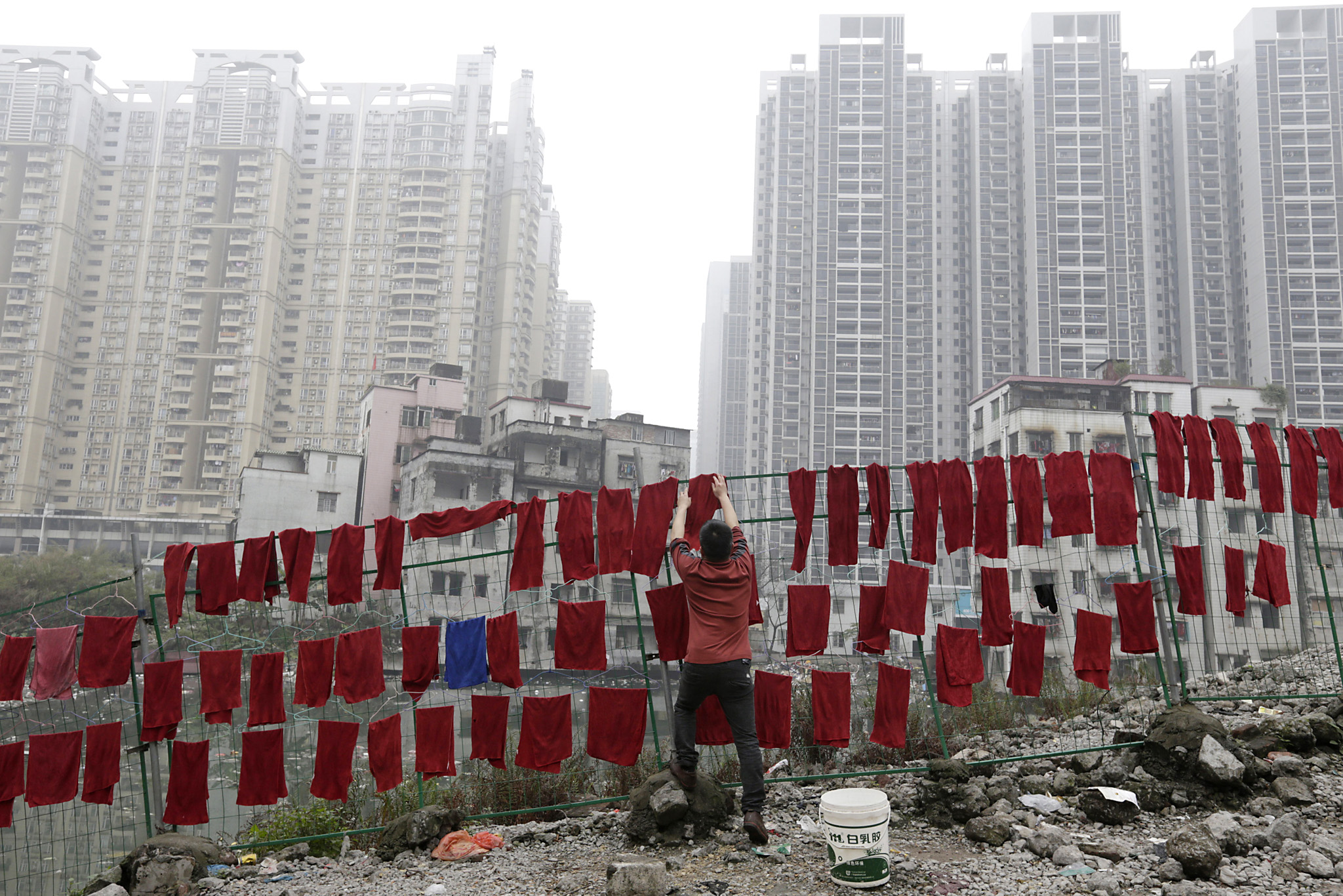 A man hangs towers on fences in an abandoned village near buildings of a residential compound in Guangzhou...A man hangs towers on fences in an abandoned village near buildings of a residential compound in Guangzhou, Guangdong Province, China, March 18, 2016. REUTERS/David Johnson