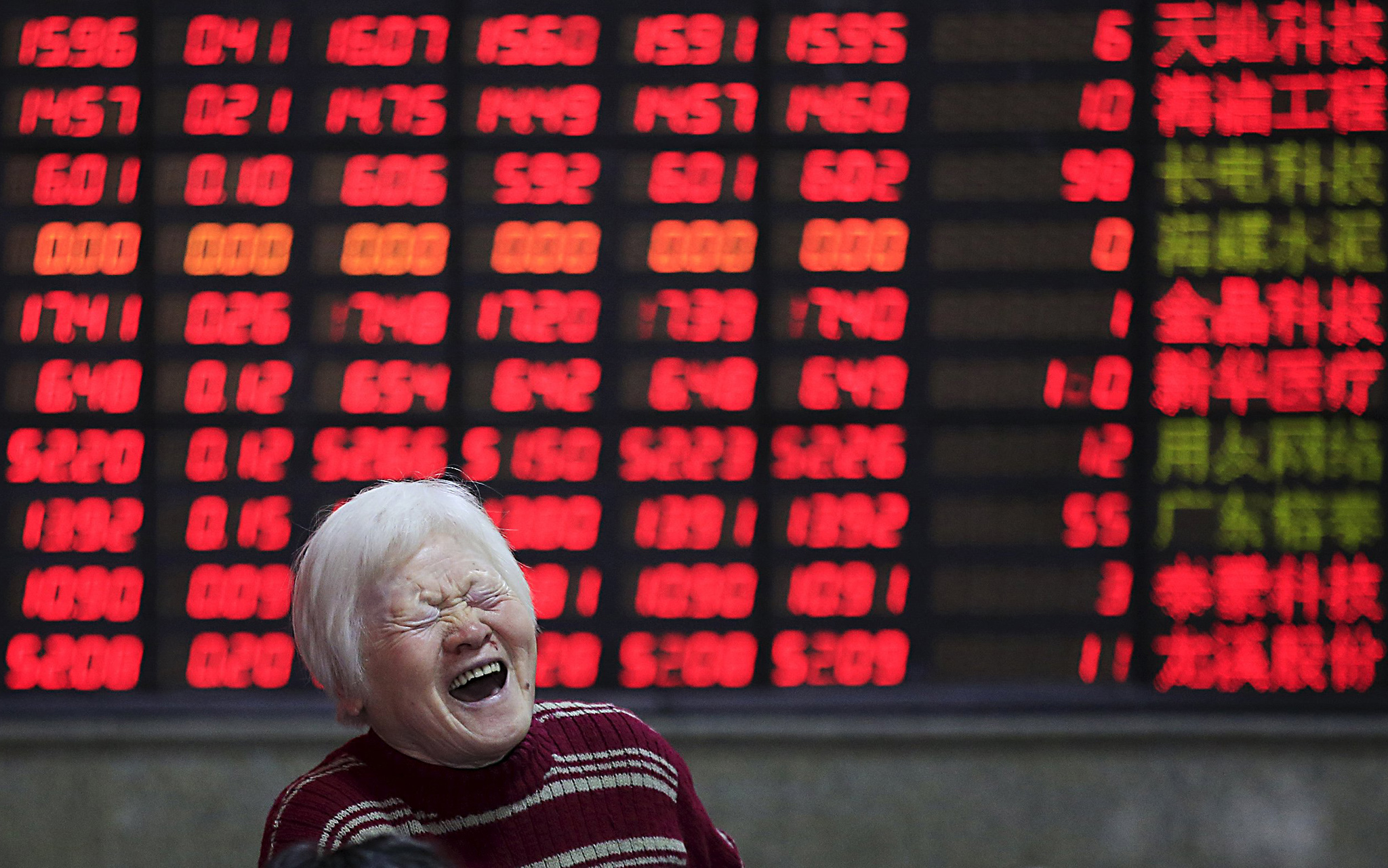 An investor smiles in front of an electronic board showing stock information at a brokerage house in Shanghai...An investor reacts in front of an electronic board showing stock information at a brokerage house in Shanghai, China, March 7, 2016. REUTERS/Aly Song