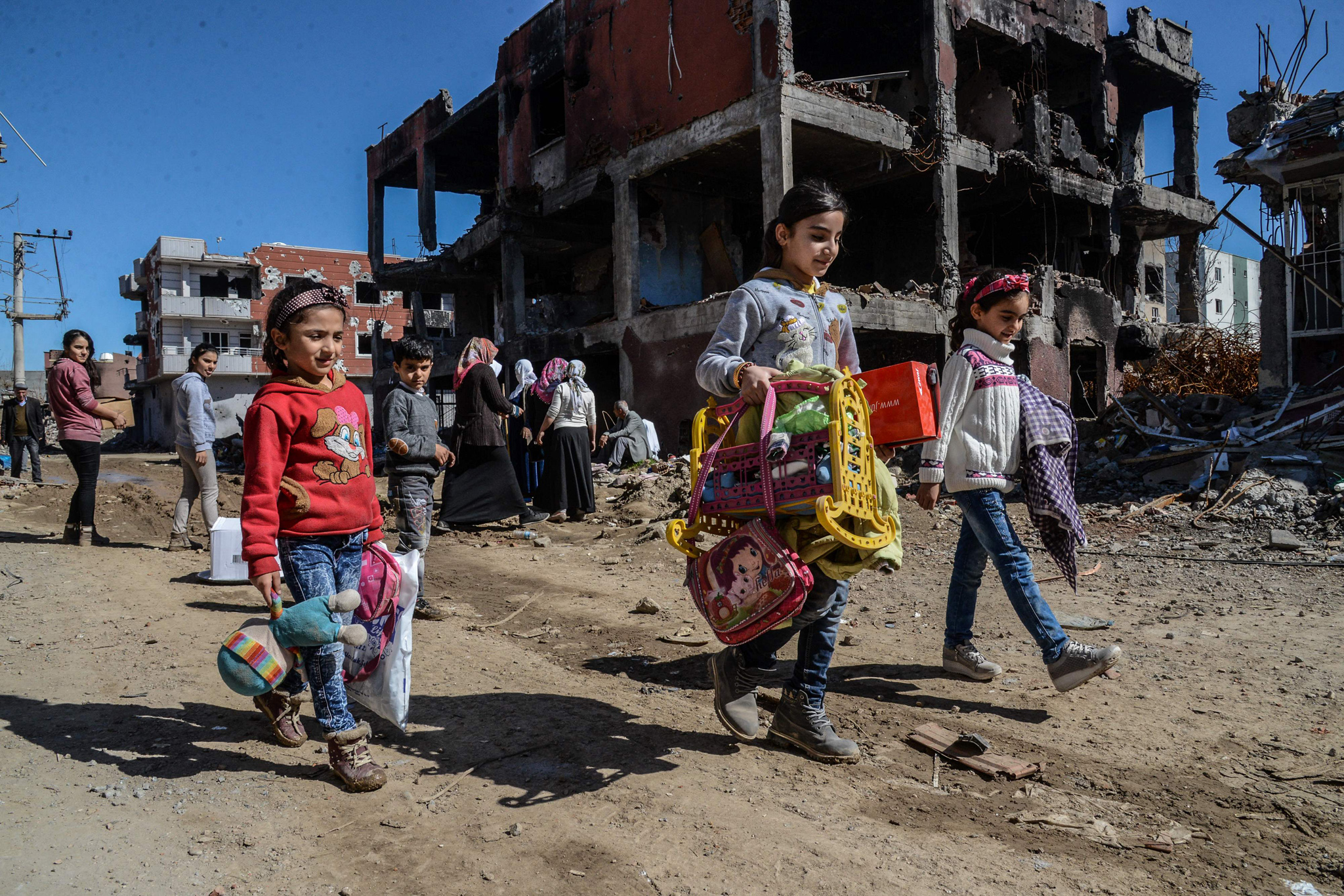 Young girls walk next to ruined houses a...Young girls walk next to ruined houses and shops on March 8, 2016 during International Women's day in Cizre district. Residents of Cizre in southeastern Turkey began returning home Wednesday after authorities partially lifted a curfew in place since December for a controversial operation against Kurdish rebels which left many homes destroyed. / AFP / ILYAS AKENGINILYAS AKENGIN/AFP/Getty Images