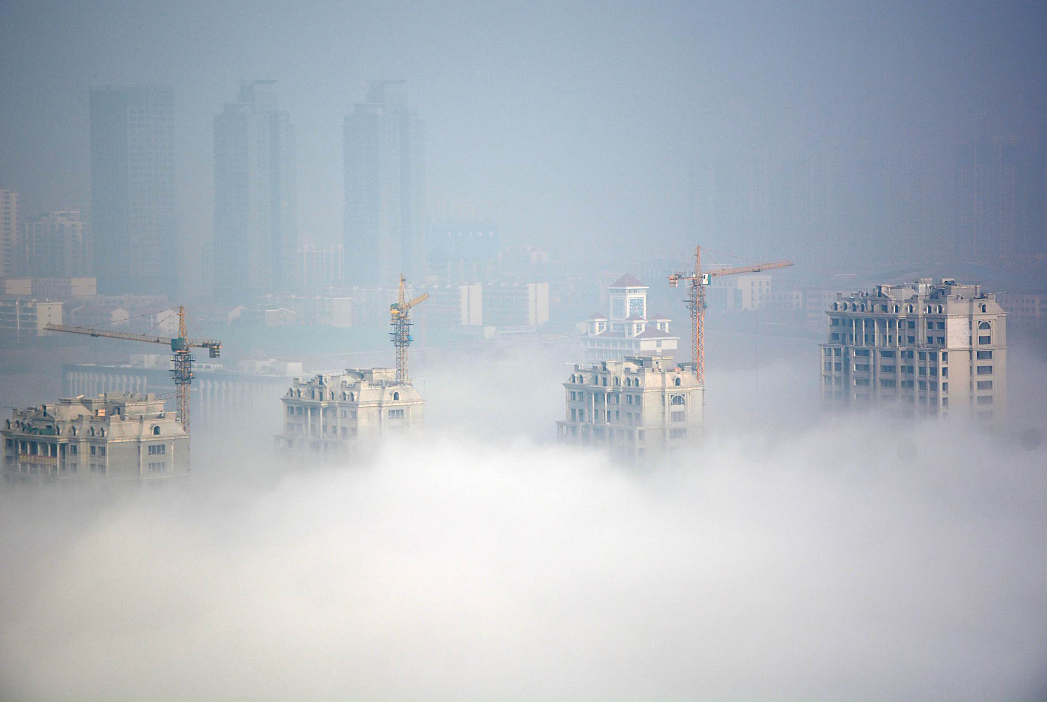 Buildings under construction are seen during a hazy day in Rizhao...Buildings under construction are seen during a hazy day in Rizhao, Shandong Province, China, March 15, 2016. REUTERS/Stringer ATTENTION EDITORS - THIS PICTURE WAS PROVIDED BY A THIRD PARTY. THIS PICTURE IS DISTRIBUTED EXACTLY AS RECEIVED BY REUTERS, AS A SERVICE TO CLIENTS. CHINA OUT. NO COMMERCIAL OR EDITORIAL SALES IN CHINA.       TPX IMAGES OF THE DAY
