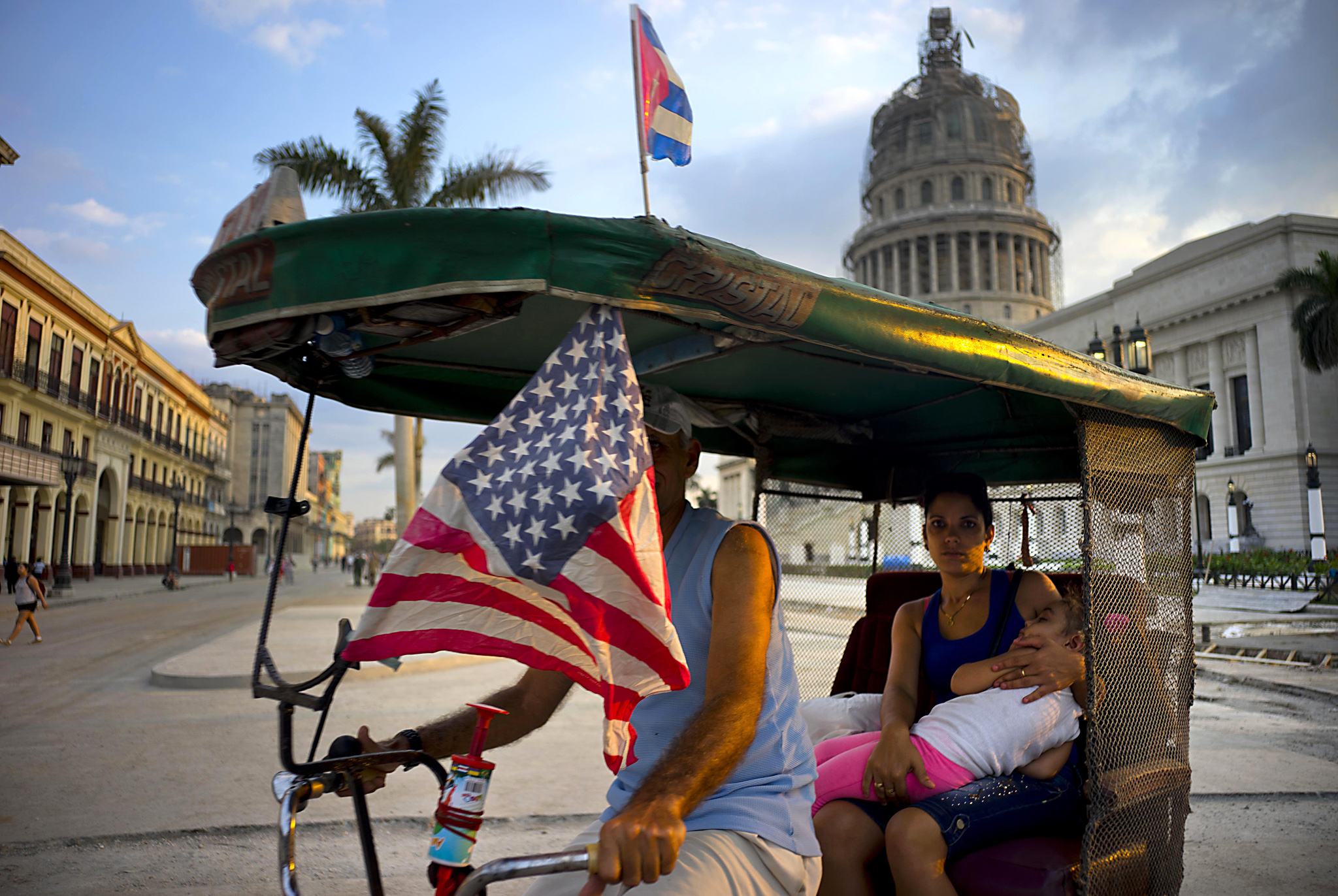 A taxi pedals his bicycle, decorated with Cuban and U.S. flags, as he transports a woman holding a sleeping girl, near the Capitolio in Havana, Cuba, Tuesday, March 15, 2016. President Barack Obama will travel to Cuba on March 20. (AP Photo/Ramon Espinosa)