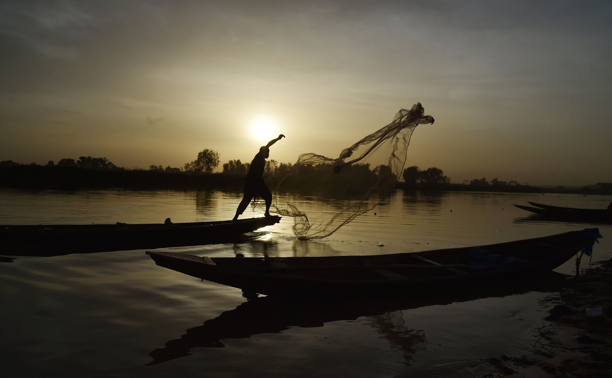 TOPSHOT - A fisherman works on the Niger...TOPSHOT - A fisherman works on the Niger river on March 21, 2016 in Niamey.