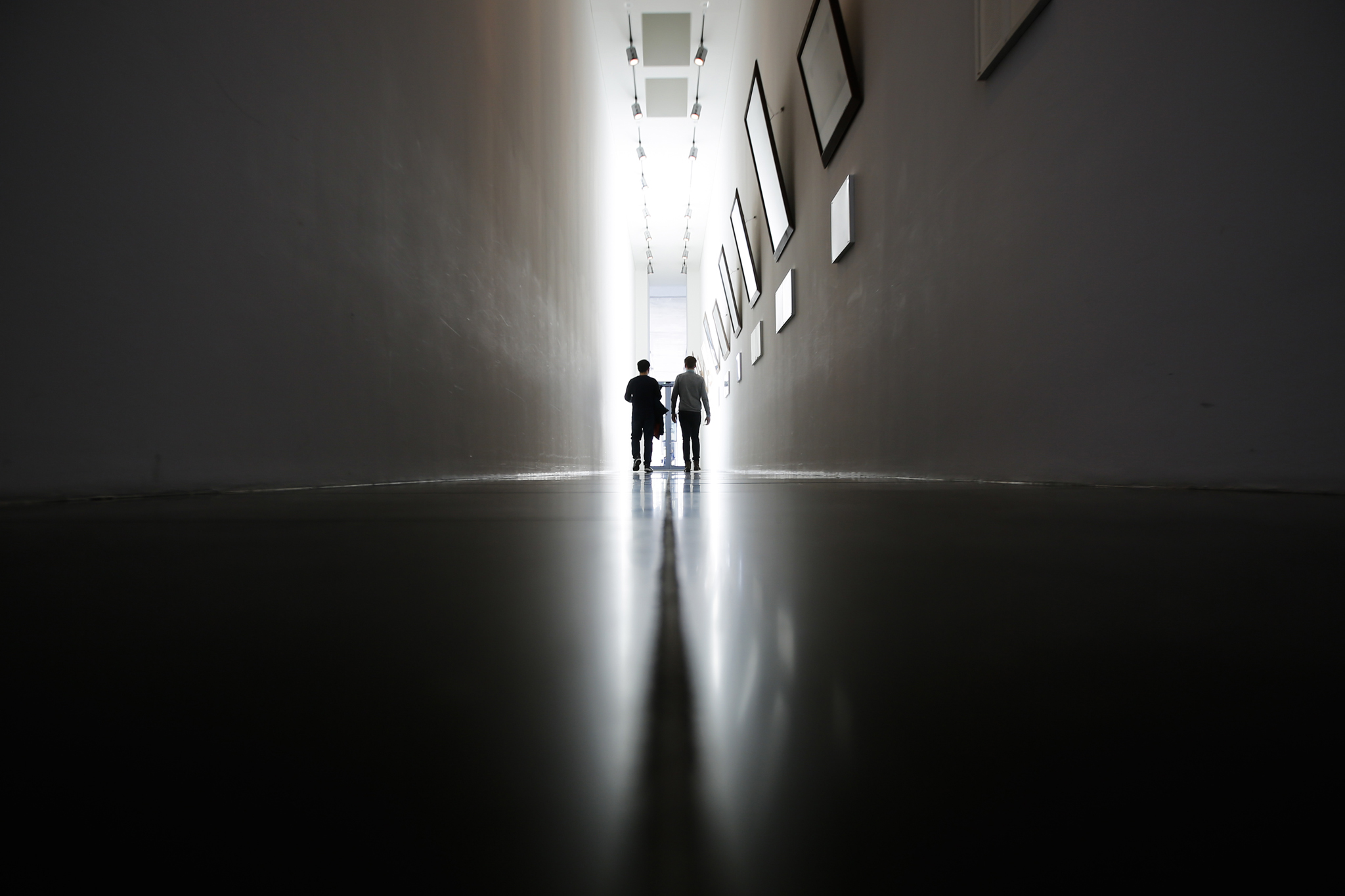 Two men silhouette in front of a bright sunny glas door in a corridor of a German parliament building in Berlin, Germany, Thursday, March 17, 2016. (AP Photo/Markus Schreiber)