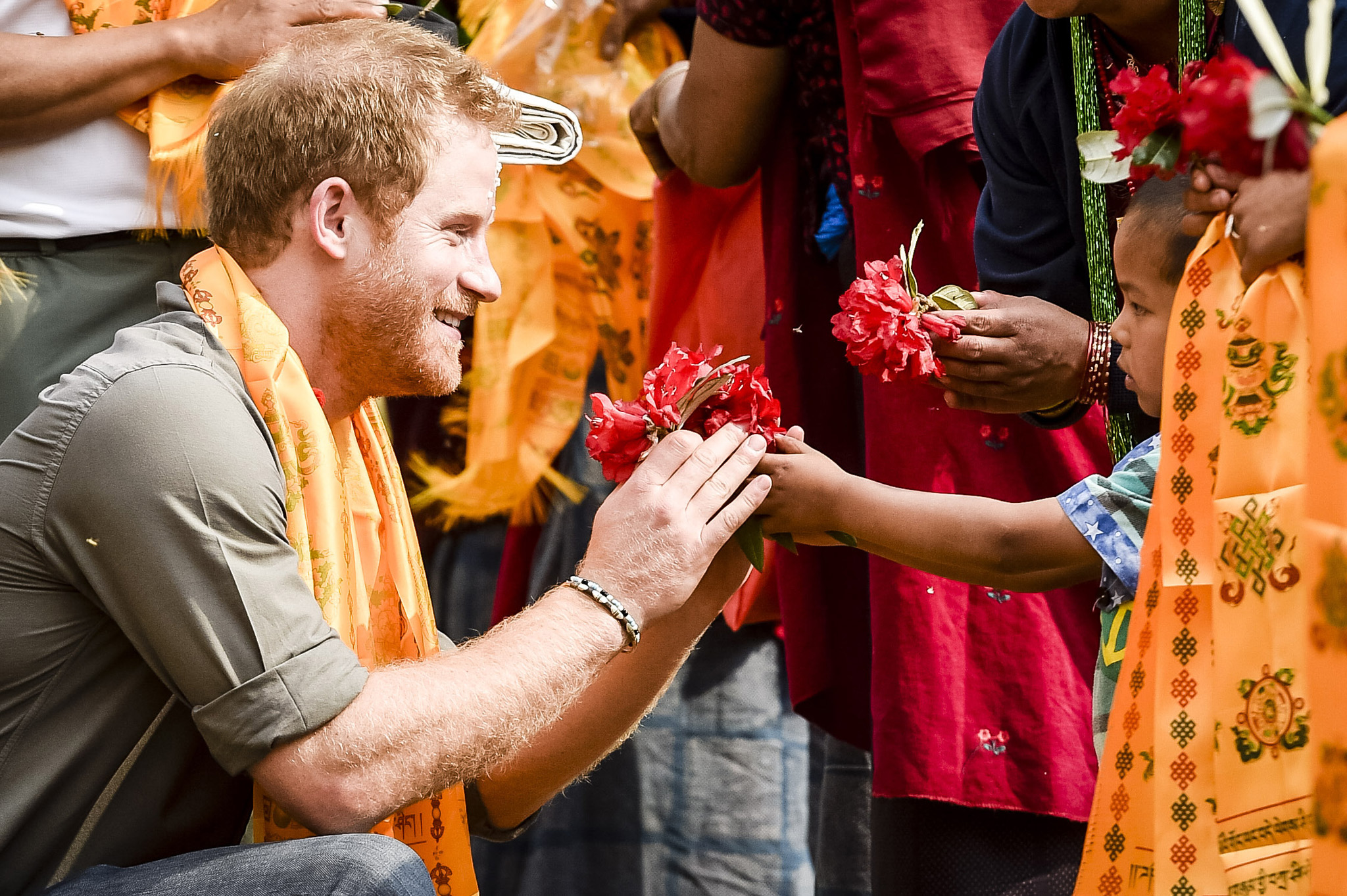 Prince Harry Visits Nepal - Day 3...Prince Harry kneels to receive flowers from children villagers from Bhir Kuna as the Prince arrives at the earthquake struck village in Nepal. PRESS ASSOCIATION Photo. Picture date: Monday March, 21, 2016. See PA story ROYAL Harry. Photo credit should read: Ben Birchall/PA Wire