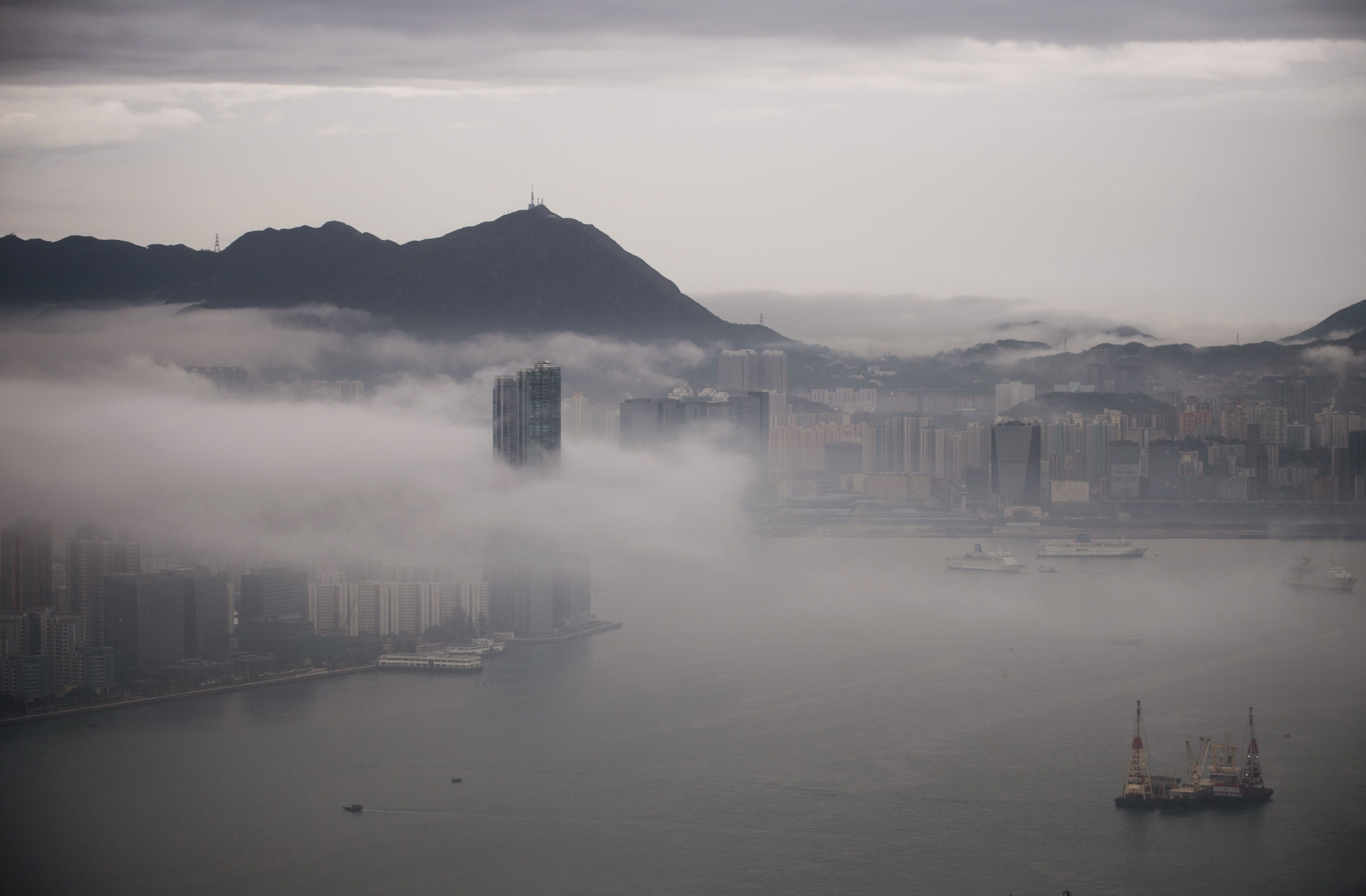 This general view shows a layer of fog d...This general view shows a layer of fog descending upon buildings in the Kowloon district (L) of Hong Kong as ships sail in Victoria Harbour on March 23, 2016. / AFP PHOTO / Anthony WALLACEANTHONY WALLACE/AFP/Getty Images