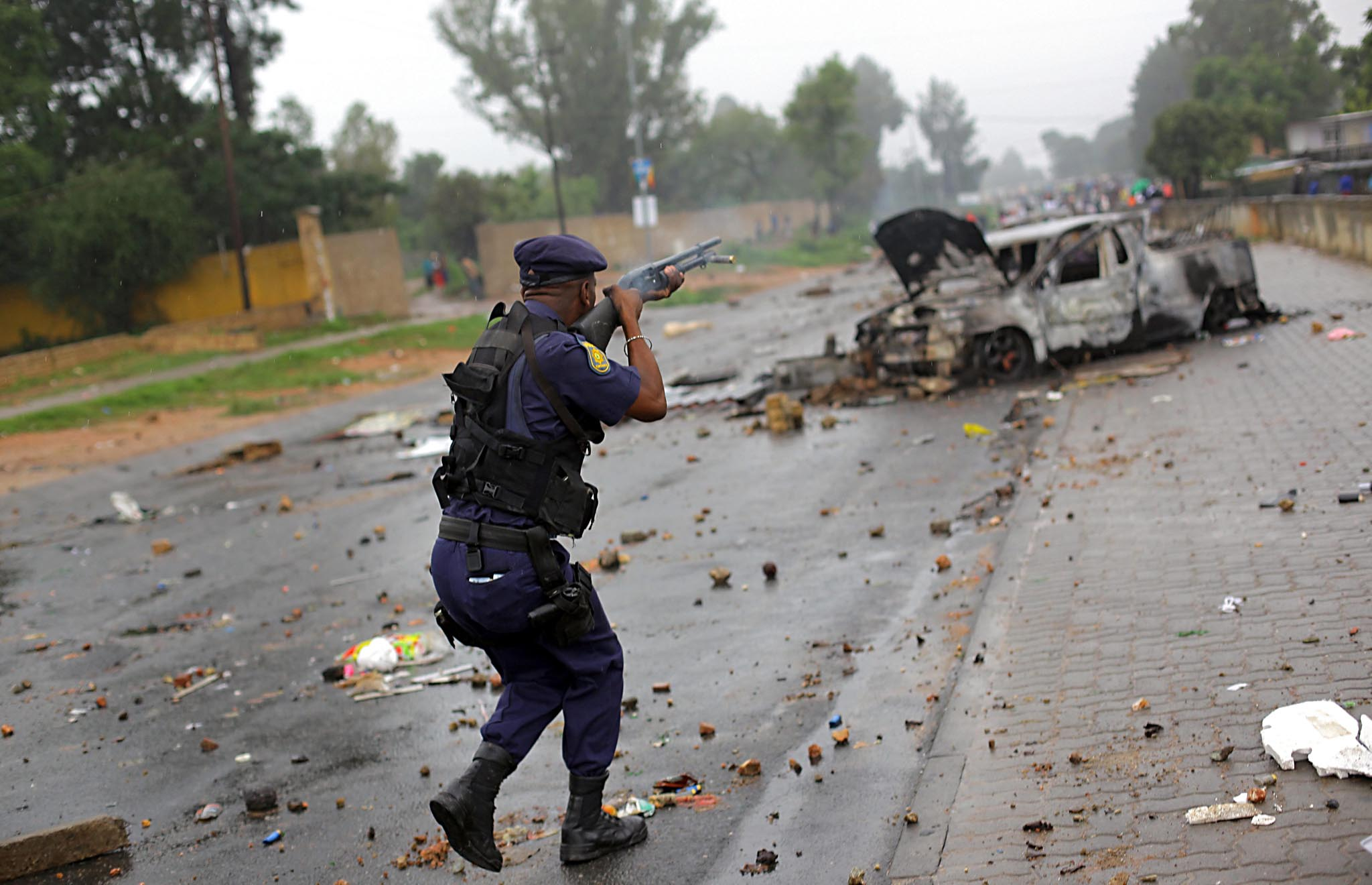 Johannesburg Electricity Protests...epa05215589 A member of the South African Police Service fires rubber bullets on striking community members in Zandspruit, an informal settlement west of Johannesburg, South Africa, 17 March 2016. Community members blocked and barricaded roads surrounding the settlement, after their illegal electricity connections where removed my Johannesburg Council workers almost a week ago.  EPA/KEVIN SUTHERLAND