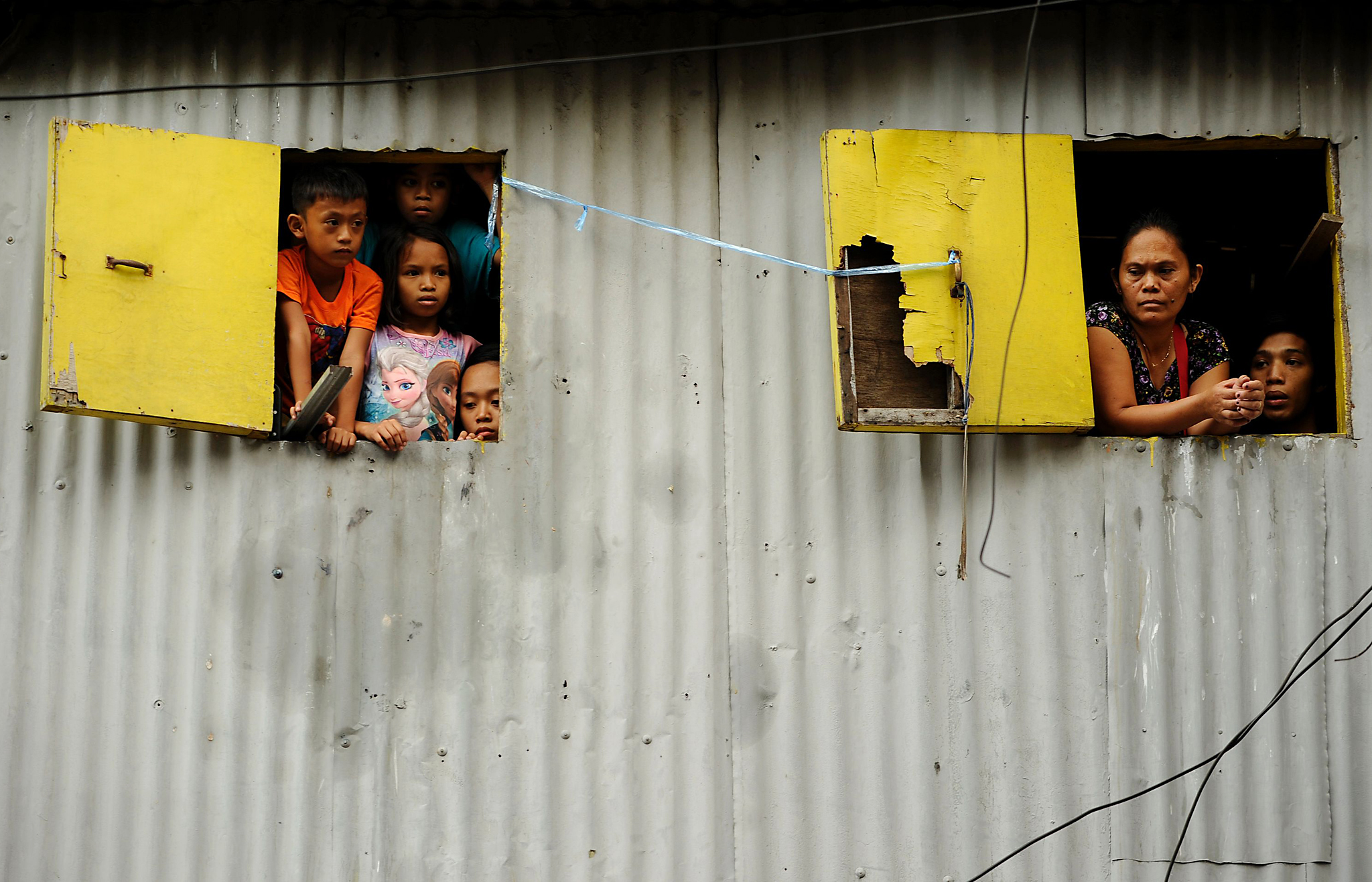 Residents look out of windows as the she...Residents look out of windows as the sheriff (not seen) of a demolition team negotiates to avoid violence during the demolition of an informal settlers' community in Manila on March 18, 2016.   Shantytowns dot the Philippine capital where many of the city's poor are forced to reside. / AFP PHOTO / NOEL CELISNOEL CELIS/AFP/Getty Images