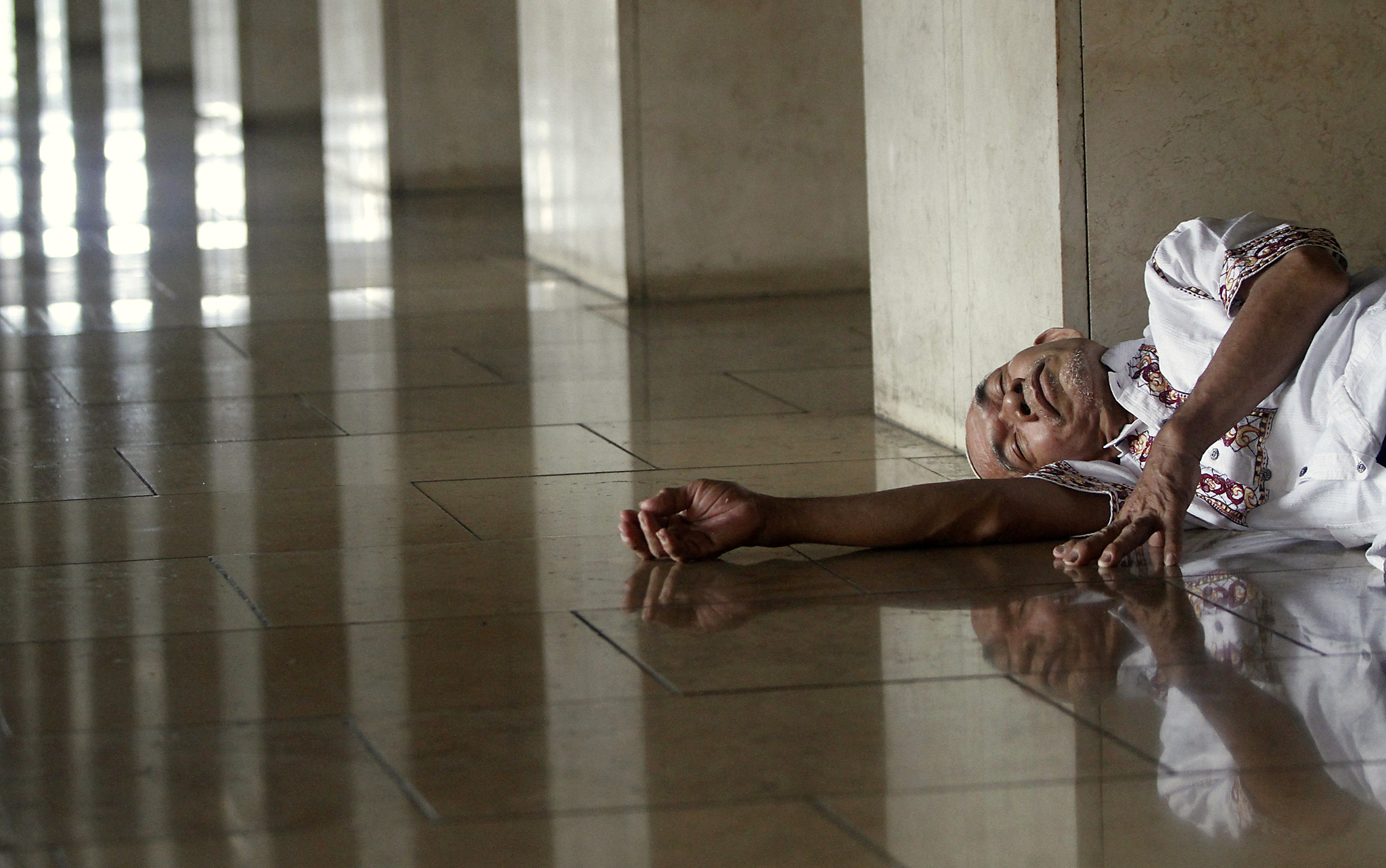 A man rests before attending Friday prayers at Istiqlal Mosque in Jakarta...A man rests before attending Friday prayers at Istiqlal Mosque in Jakarta, Indonesia March 18, 2016. REUTERS/Garry Lotulung