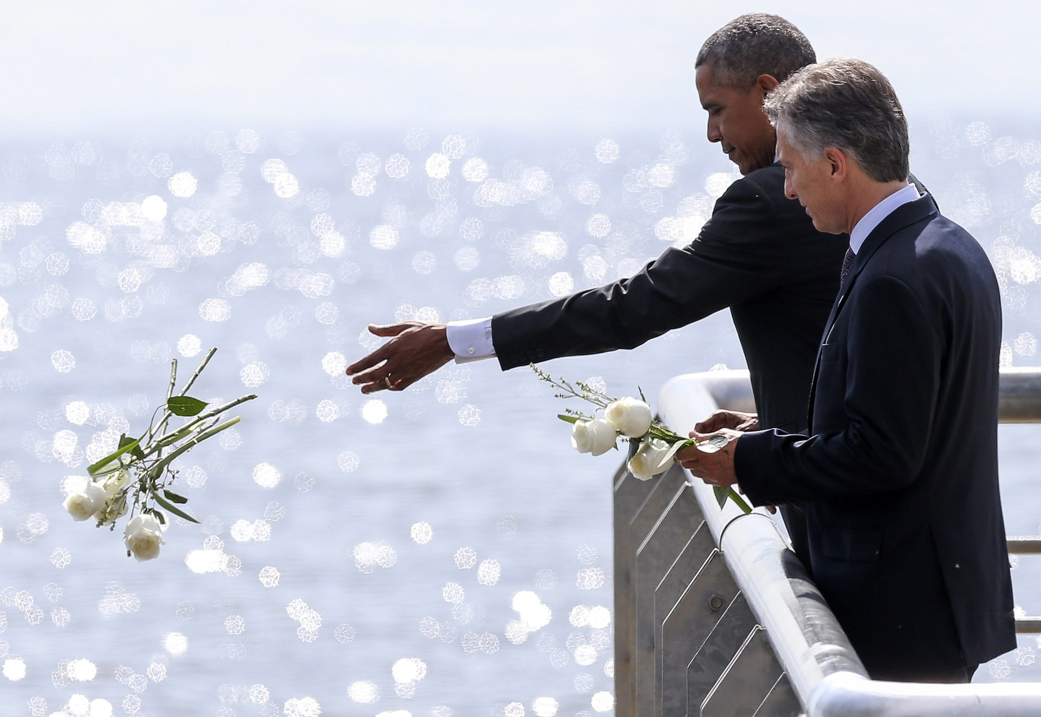 US President Obama visits Argentina...epa05229215 US President Barack Obama (L) and his counterpart from Argentina Mauricio Macri (R) make a floral tribute to the victims of the military dictatorship aat Parque de la Memoria in Buenos Aires, Argentina, 24 March 2016. During the tour of the wall, next to the Rio de la plata, the leaders approached the railing, next to the runway, and threw white flowers in tribute to those who lost their lives at the military dictatorship.  EPA/DAVID FERNANDEZ