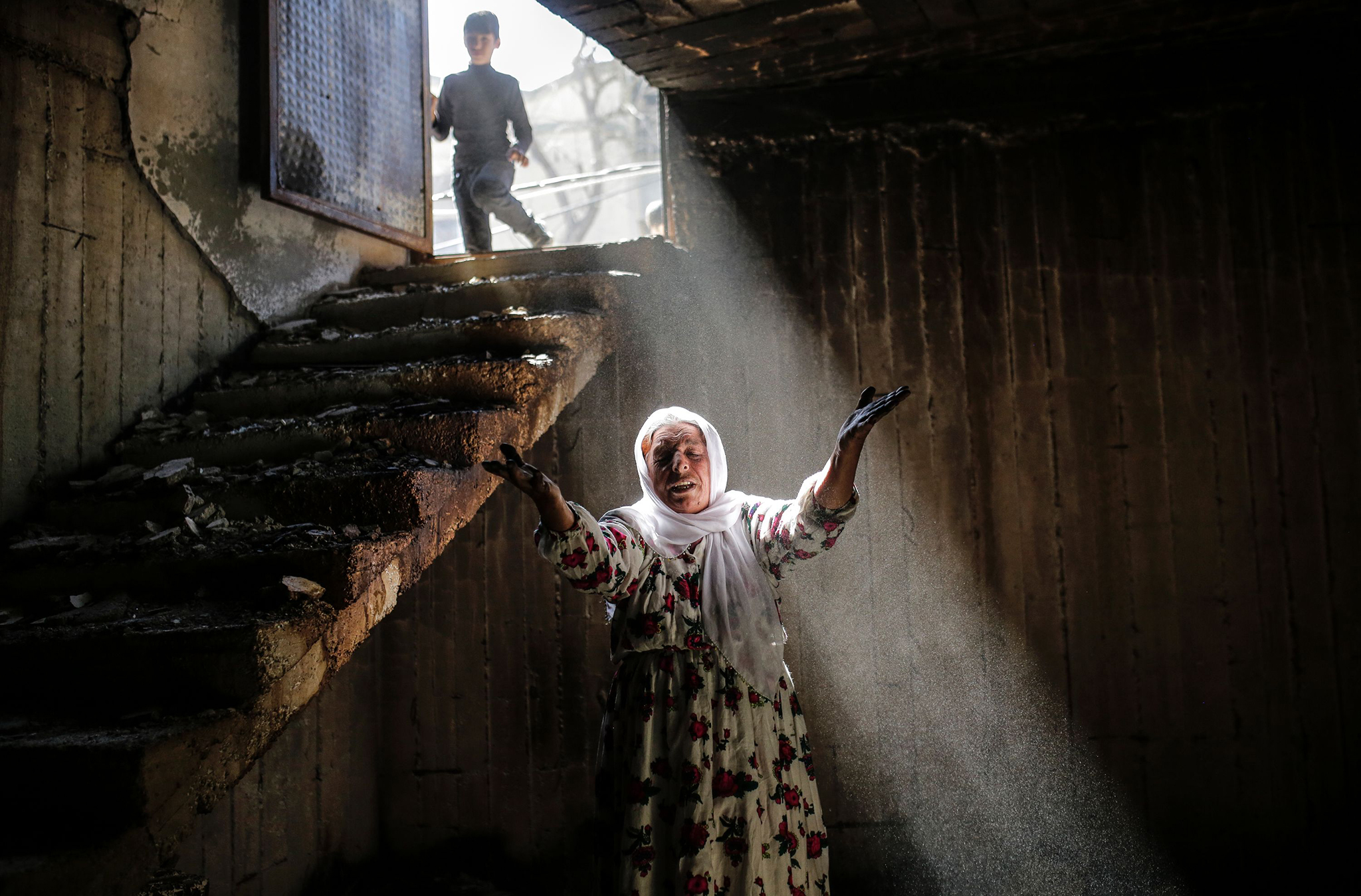 A woman reacts while walking among the ruins of damaged buildings following heavy fighting between government troops and Kurdish fighters in the southeastern Turkey Kurdish town of Cizre, near the border with Syria and Iraq.