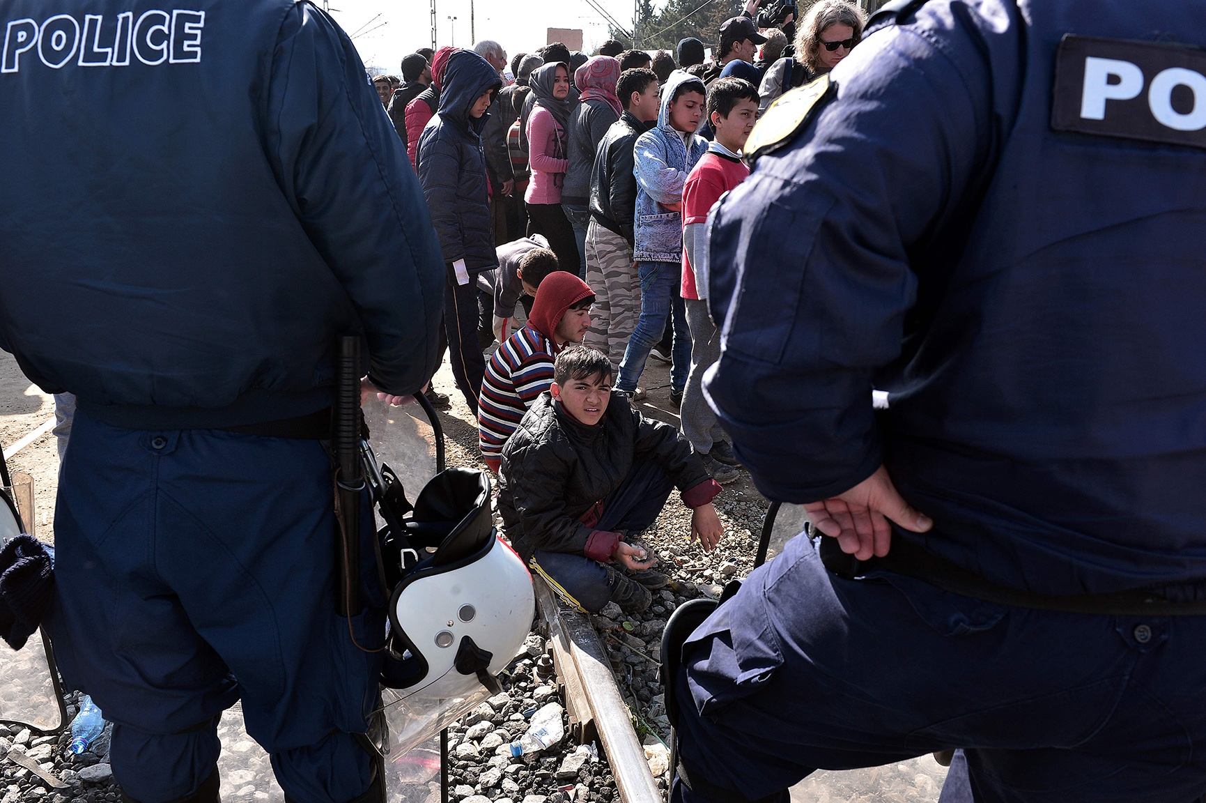 A boy looks at Greek police as refugees