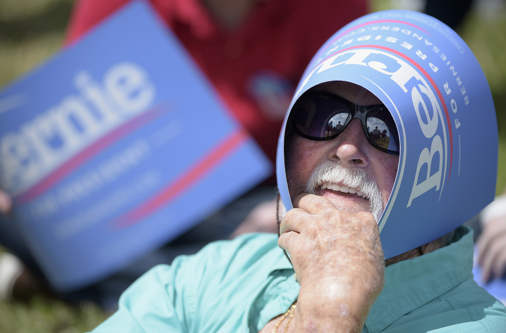 Tim Ferris shades himself from the sun while waiting in line to attend a campaign rally with Democratic presidential candidate, Sen. Bernie Sanders, in Kissimmee, Florida, USA