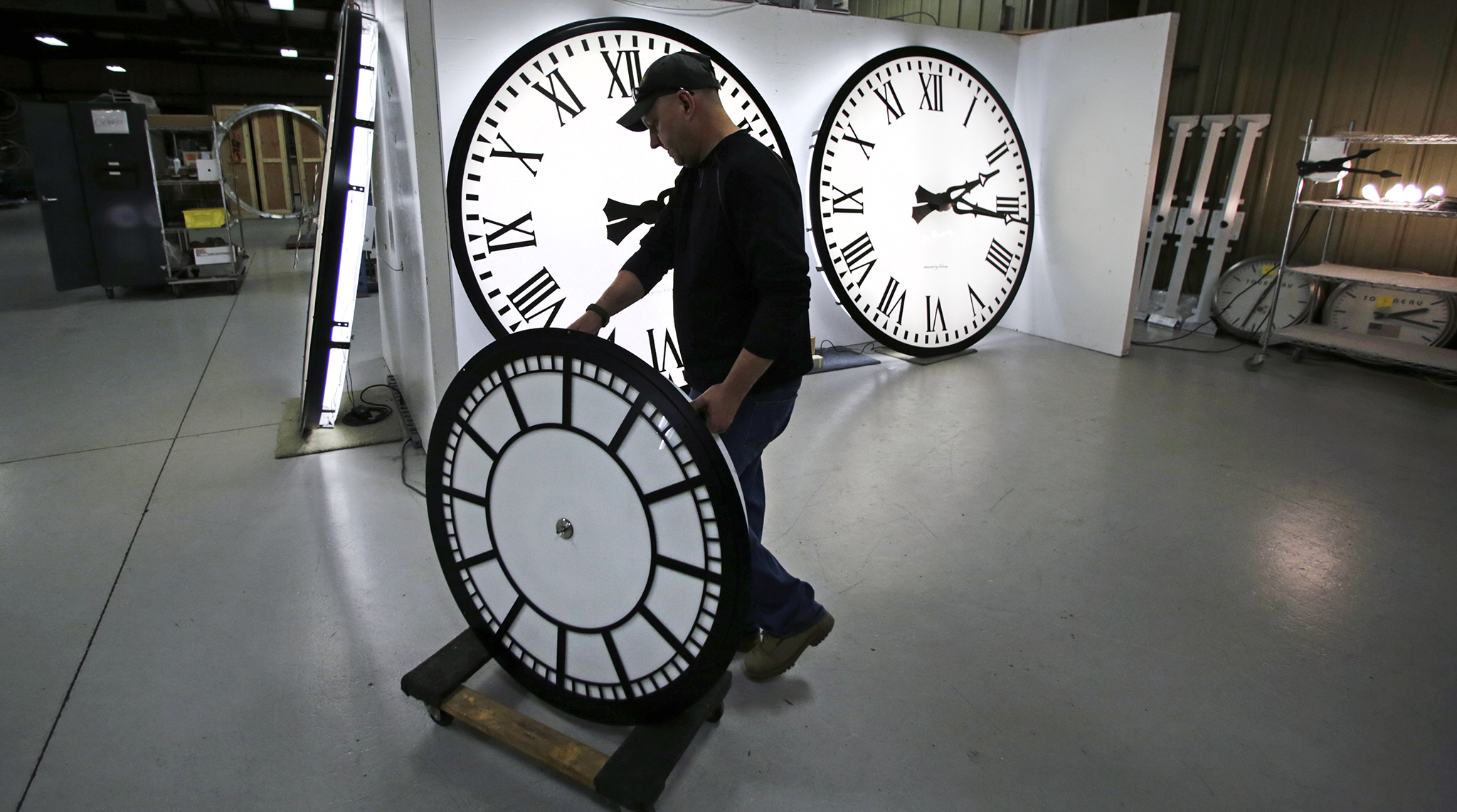 Dan LaMoore wheels a clock away from the test area as it is prepared to be shipped to a Tennessee school at the Electric Time Company in Medfield, Massachusetts.
