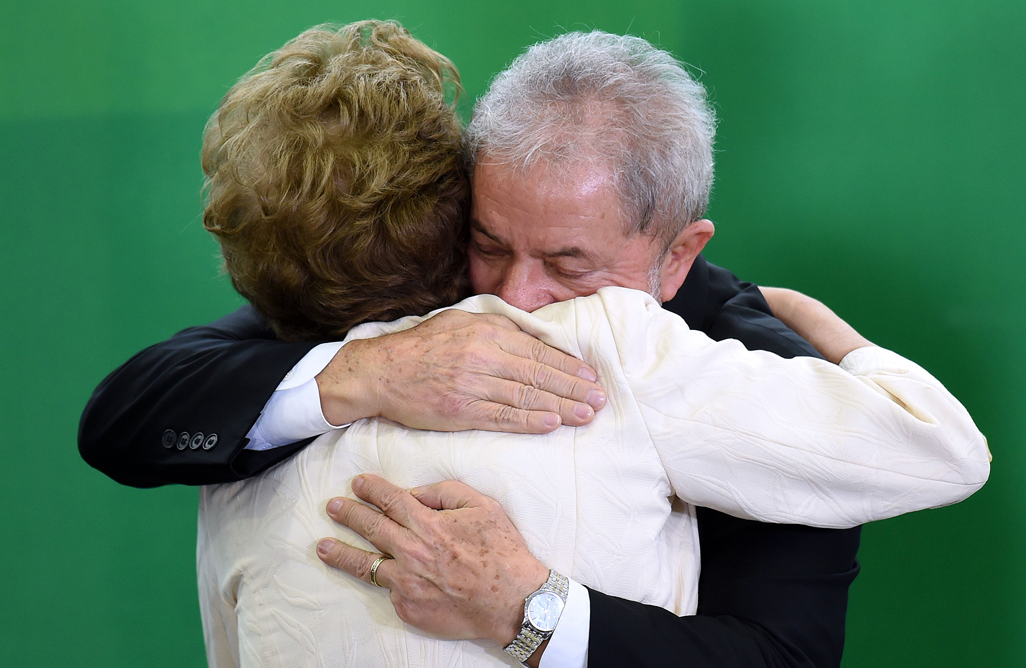 Former Brazilian president Luiz Inacio Lula da Silva hugs Brazilian president Dilma Rousseff after he swore as chief of staff in Brasilia