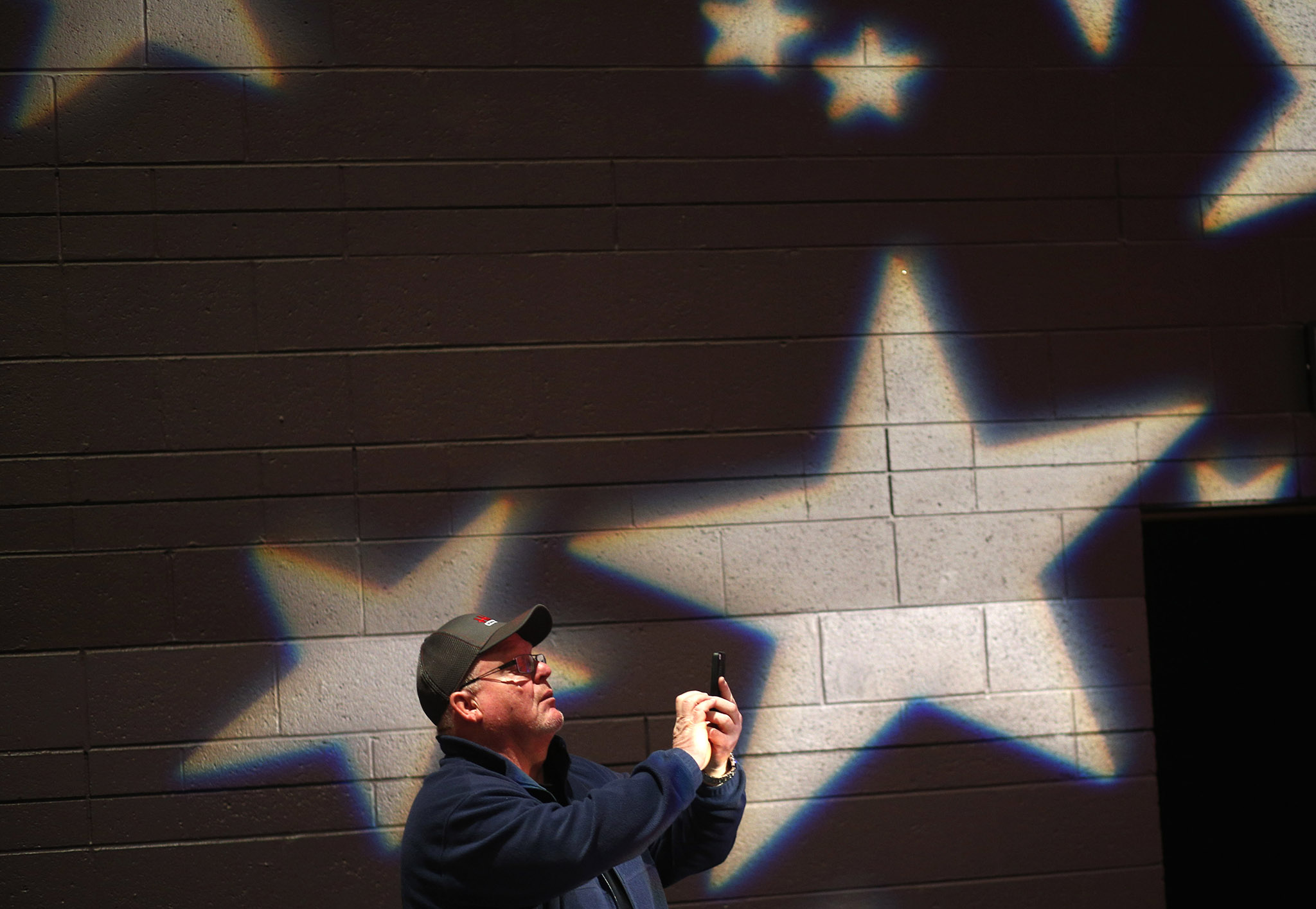 A man takes a photograph of the stage before a campaign event featuring Republican presidential candidate Donald Trump at St. Norbert College in De Pere, Wisconsin, USA