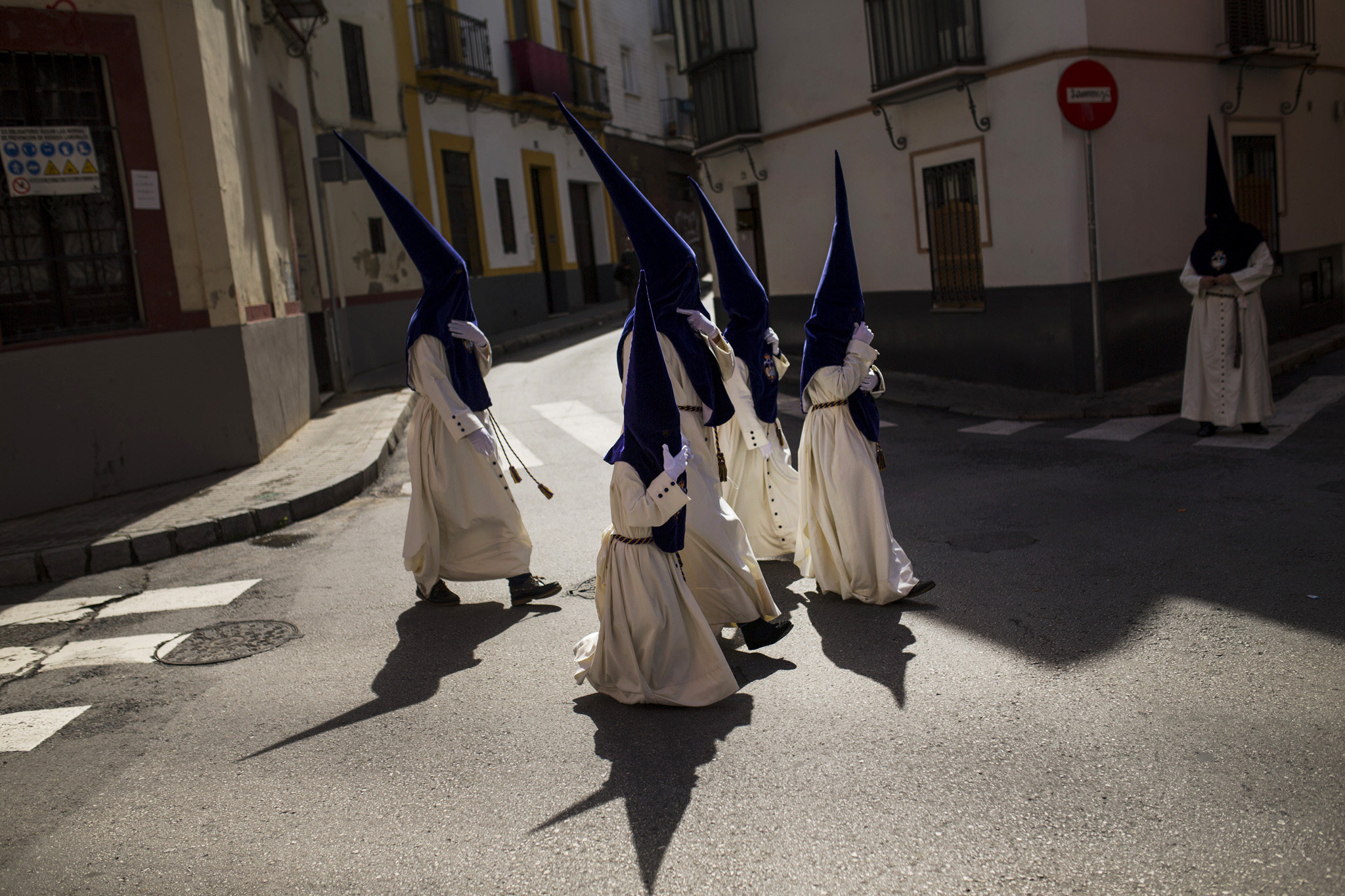 "Hooded penitents from the ""El beso de Judas"" brotherhood walk to the church to take part in a traditional annual procession in Seville, Spain, Monday, March 21, 2016. Hundreds of processions take place throughout Spain during the Easter Holy Week. (AP Photo/Francisco Seco)"