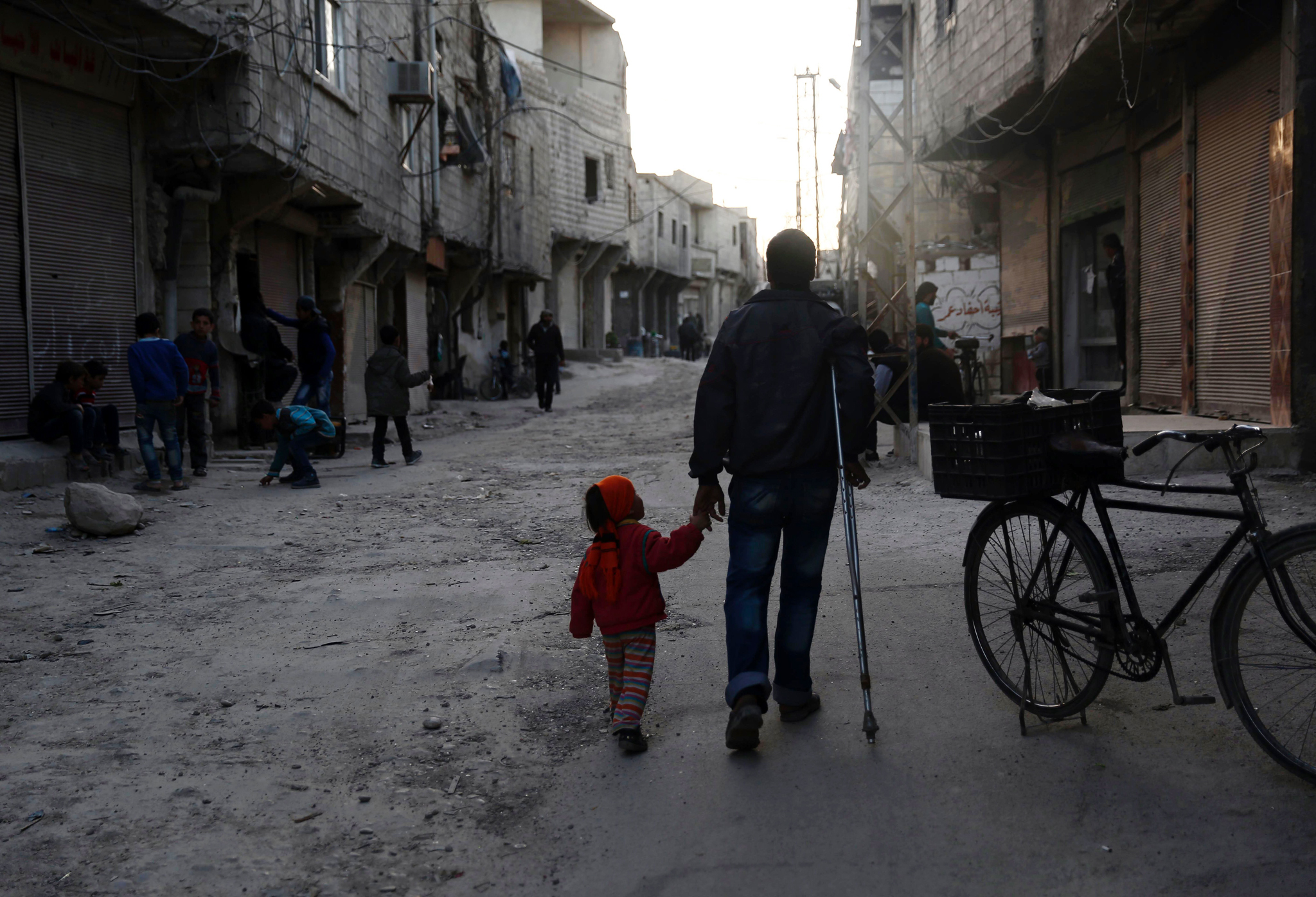 TOPSHOT - An injured Syrian man walks ho...TOPSHOT - An injured Syrian man walks holding his daughter's hand in Tishreen, a northern suburb of the capital Damascus, on March 22, 2016.  / AFP PHOTO / Sameer Al-DoumySAMEER AL-DOUMY/AFP/Getty Images