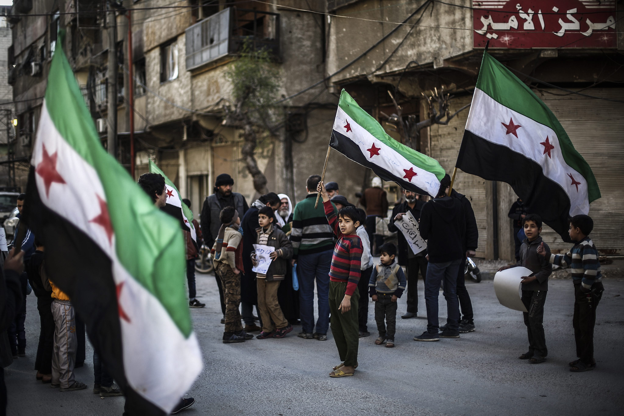 Protest against airstrikes in rebel-held city of Douma...epa05205914 Syrians wave their national flag during a protest against the airstrikes which broke the Russian-US brokered ceasefire a day before, the rebel-held city of Douma, 10 km north-east of Damascus, Syria, 11 March 2016. The ceasefire agreement enters its third week today.  EPA/MOHAMMED BADRA