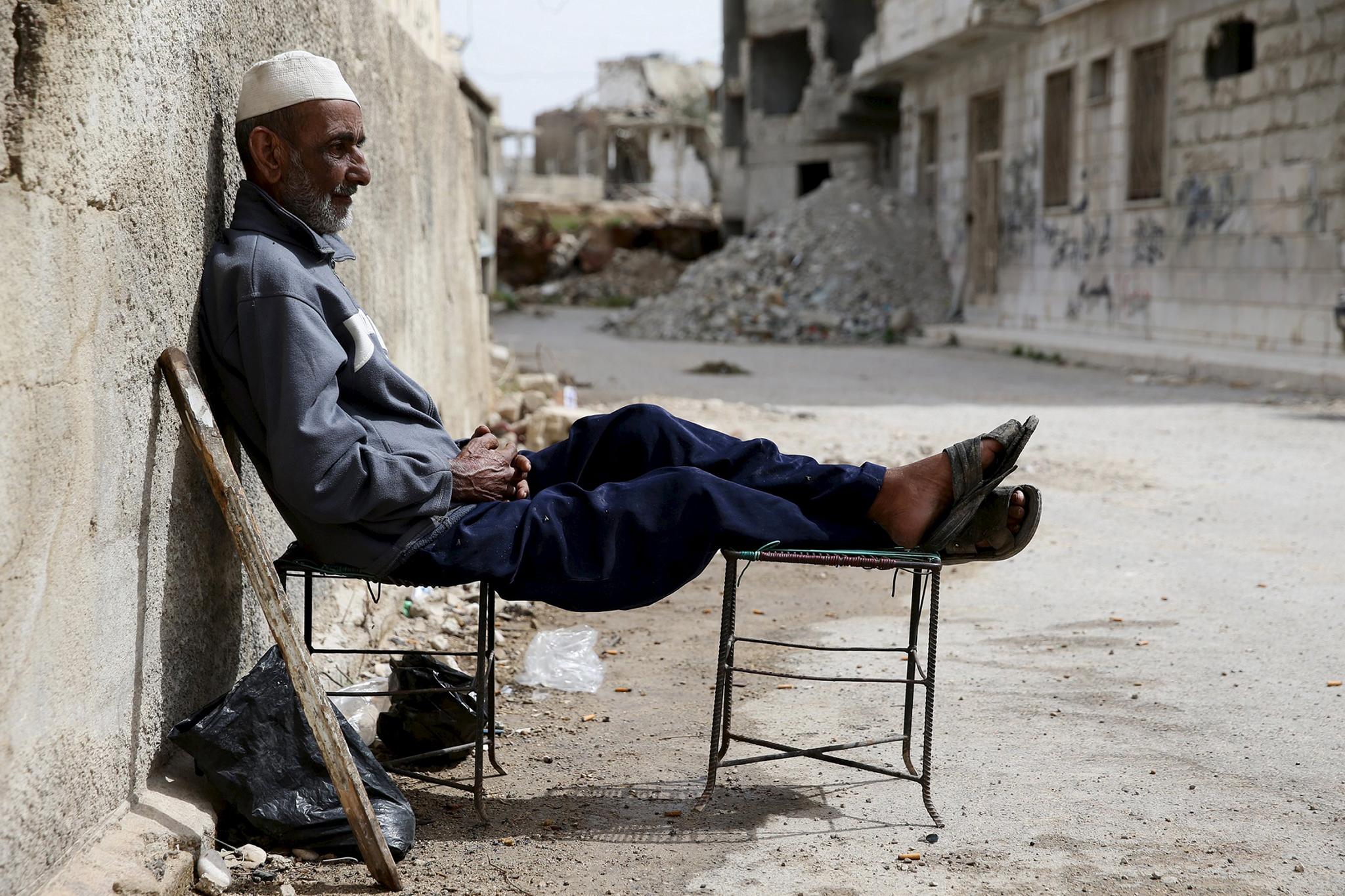 Khaled Kassmou, 70, sits along a street in the rebel held Qaboun neighborhood of Damascus...Khaled Kassmou, 70, sits along a street in the rebel held Qaboun neighborhood of Damascus, Syria March 13, 2016. Picture taken March 13, 2016. REUTERS/Bassam Khabieh