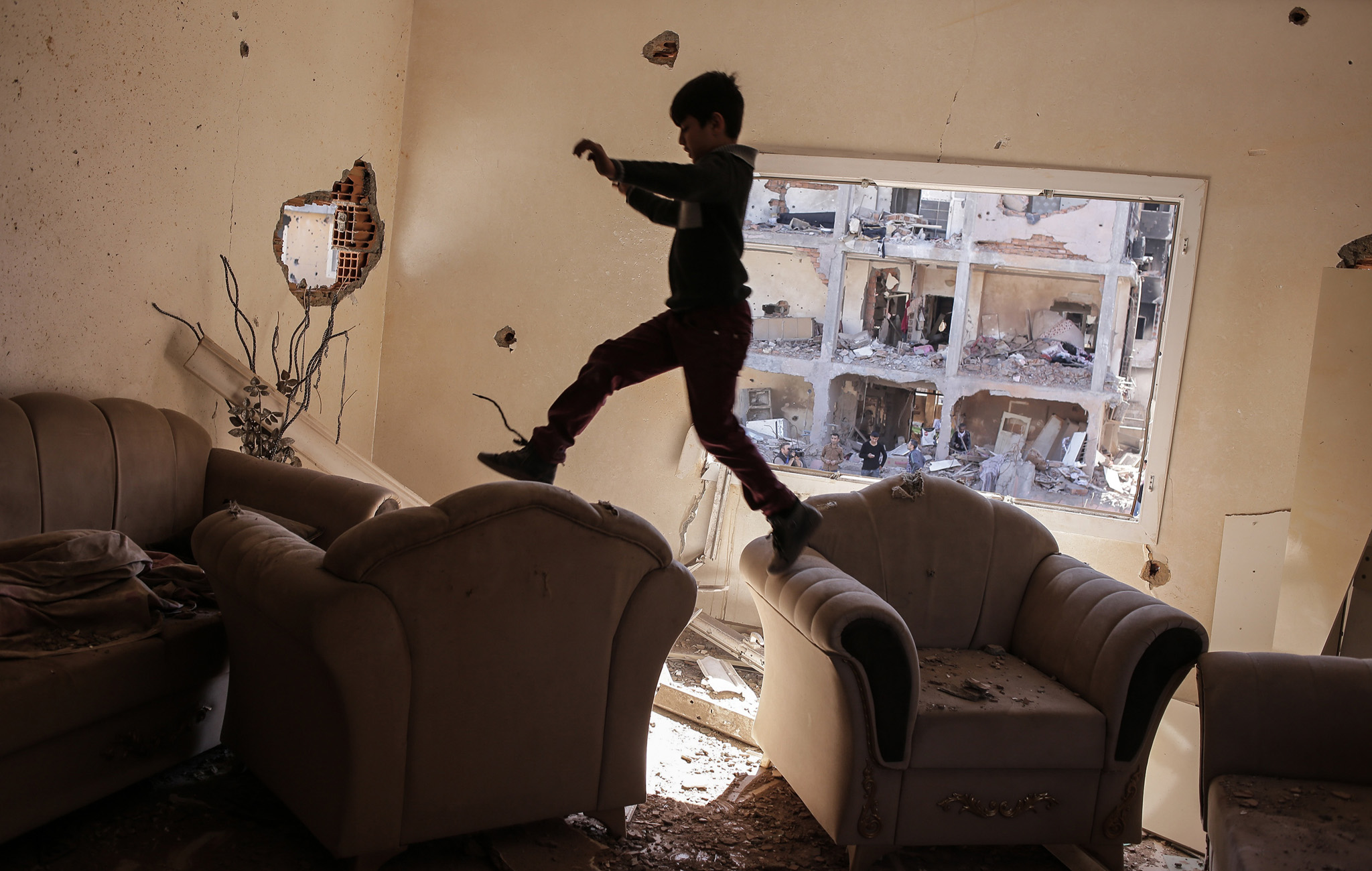 Residents Return To Turkish Town Of Cizre After Curfew...CIZRE, TURKEY - MARCH 02: A boy jumps between sofas in his ruined house on March 2, 2016 in Cizre, Turkey. Turkish authorities scaled down a 24-hour curfew imposed on the mainly Kurdish town of Cizre in southeast Turkey, nearly three weeks after declaring the successful conclusion of military operations there. The curfew was lifted at 5 a.m., allowing residents to return to their conflict-stricken neighborhoods for the first time since December 14. But it will remain in effect between 7:30 p.m. and 5 a.m. Residents began trickling back at first light, their vehicles loaded with personal belongings and, in some cases, children. (Photo by Cagdas Erdogan/Getty Images)